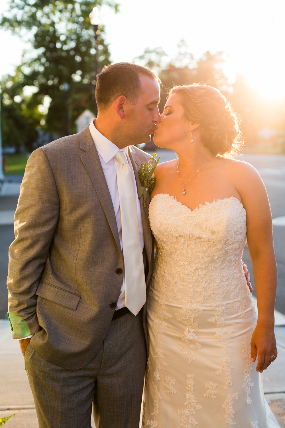 Bride and groom kiss outside at sunset.