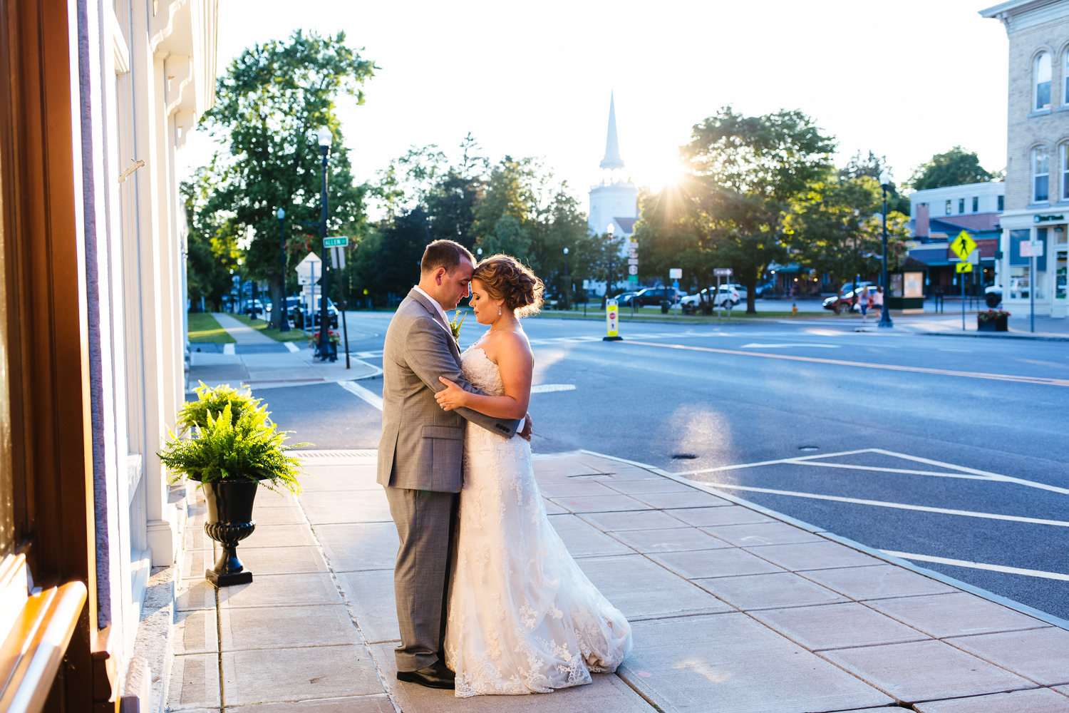 Bride and groom stand on the street corner at sunset in Cazenovia, NY.