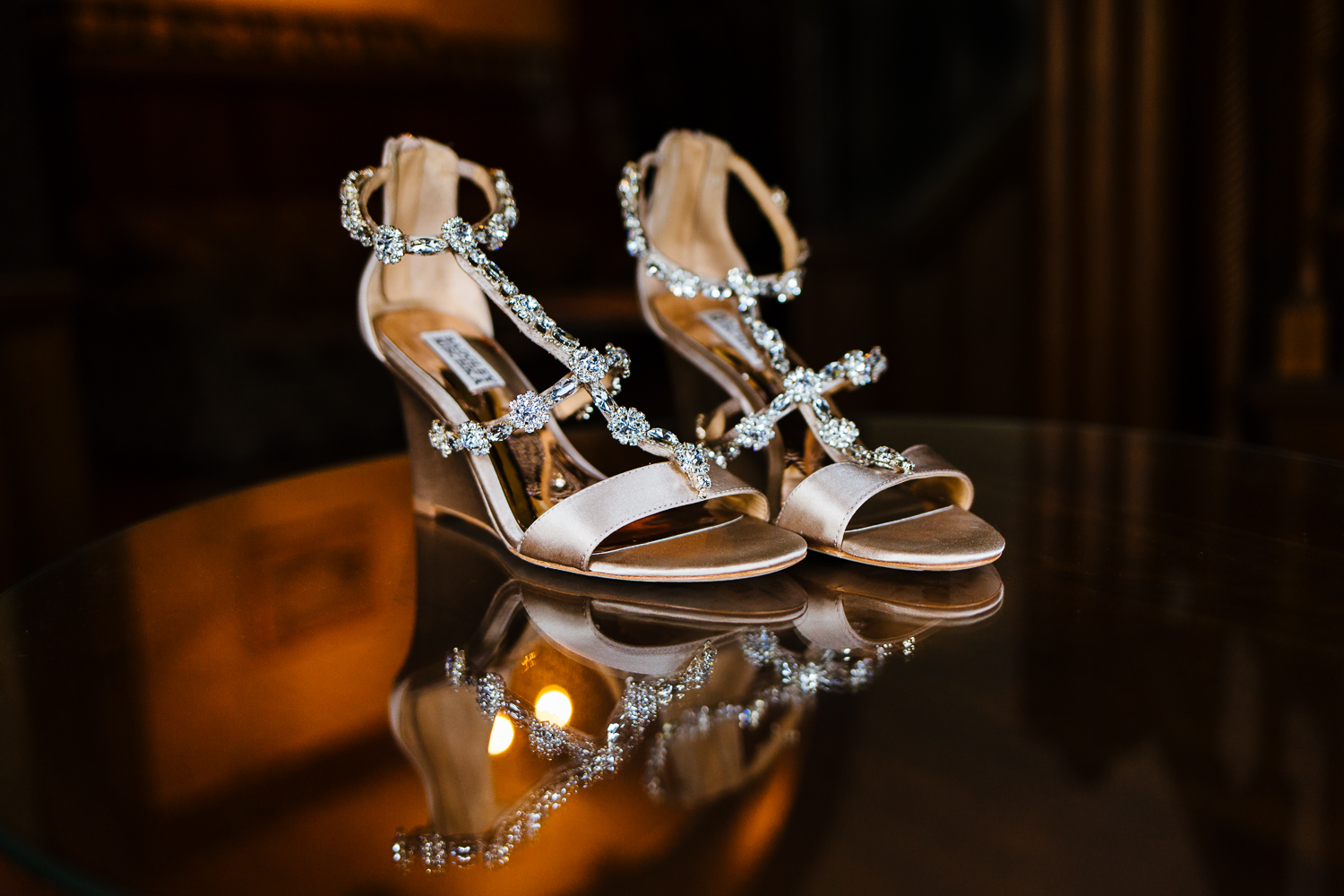 Sparkly wedding shoes reflected on glass table.