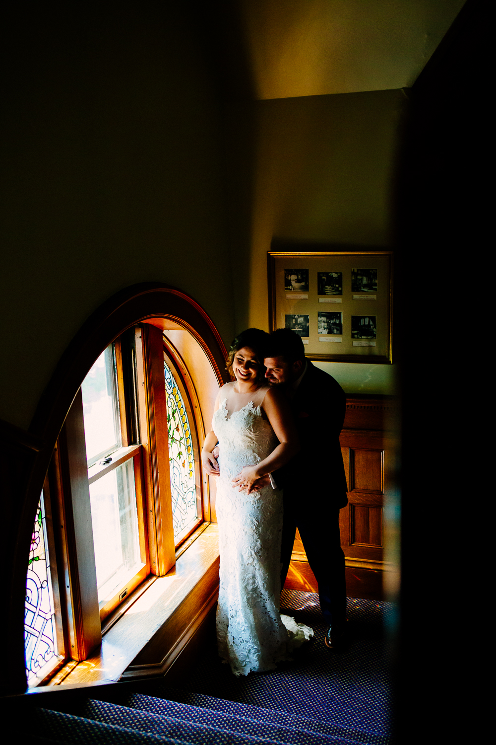 Bride and groom smile near a stained glass window.