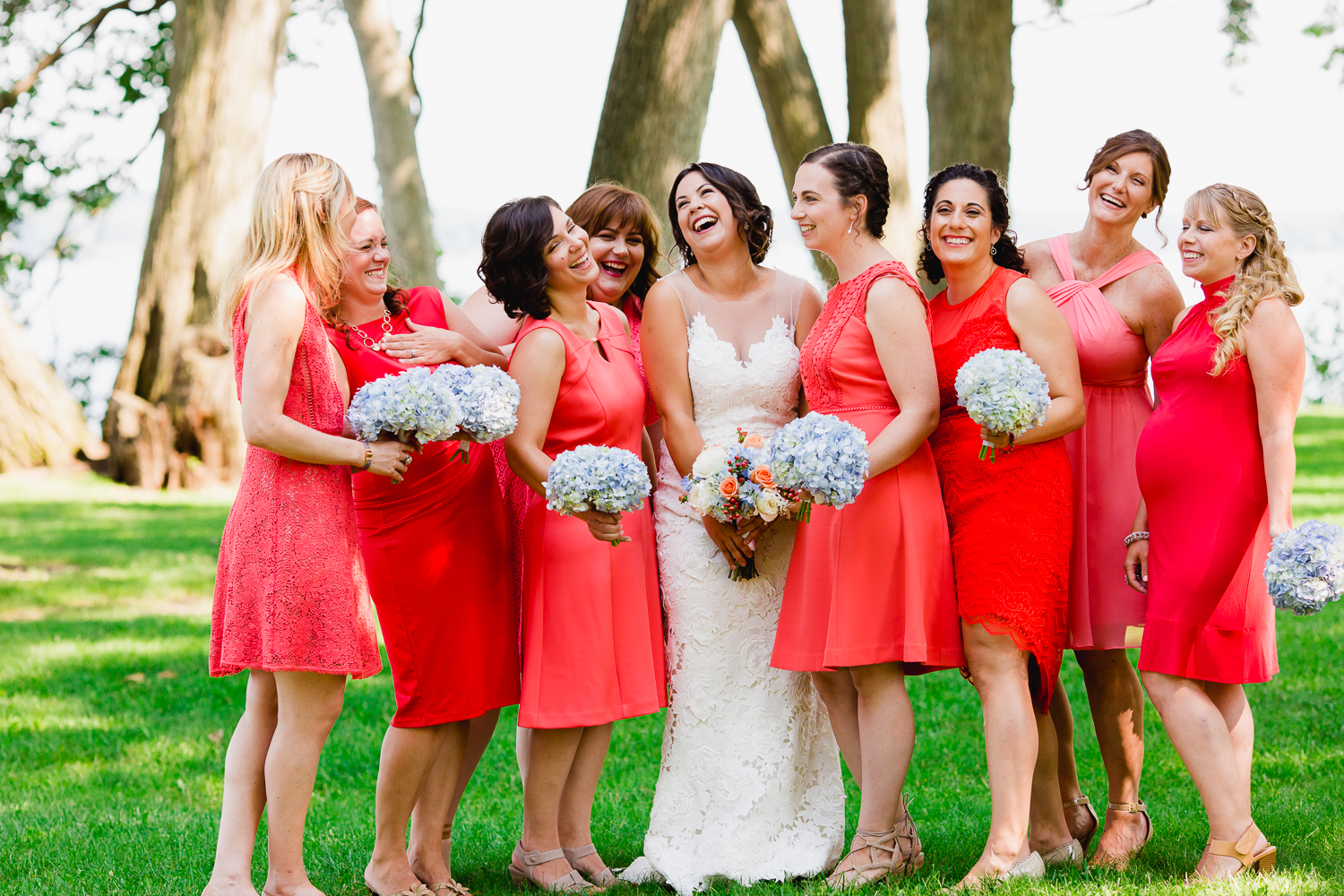 Bridesmaids in coral dresses laugh while standing around the bride.