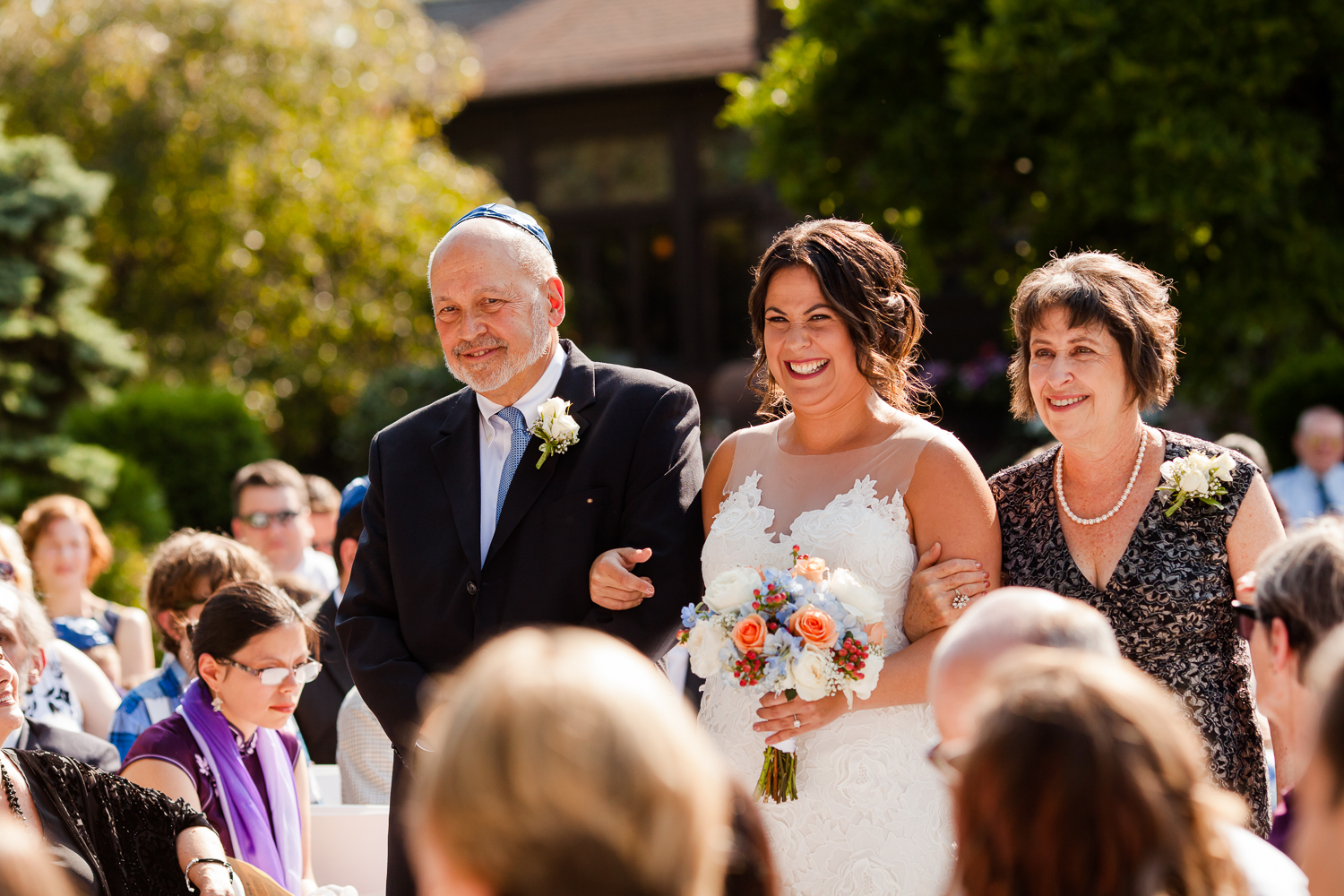 Bride smiles as she walks down the aisle with her mother and father.