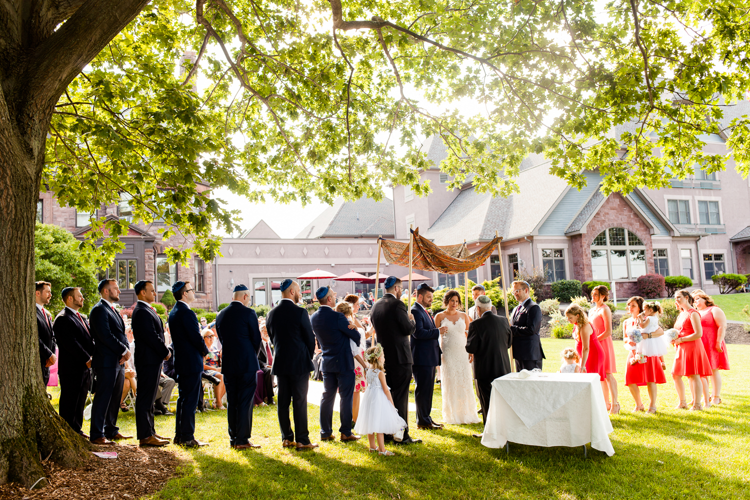 Bride and groom get married surrounded by family, friends, and bridal party.