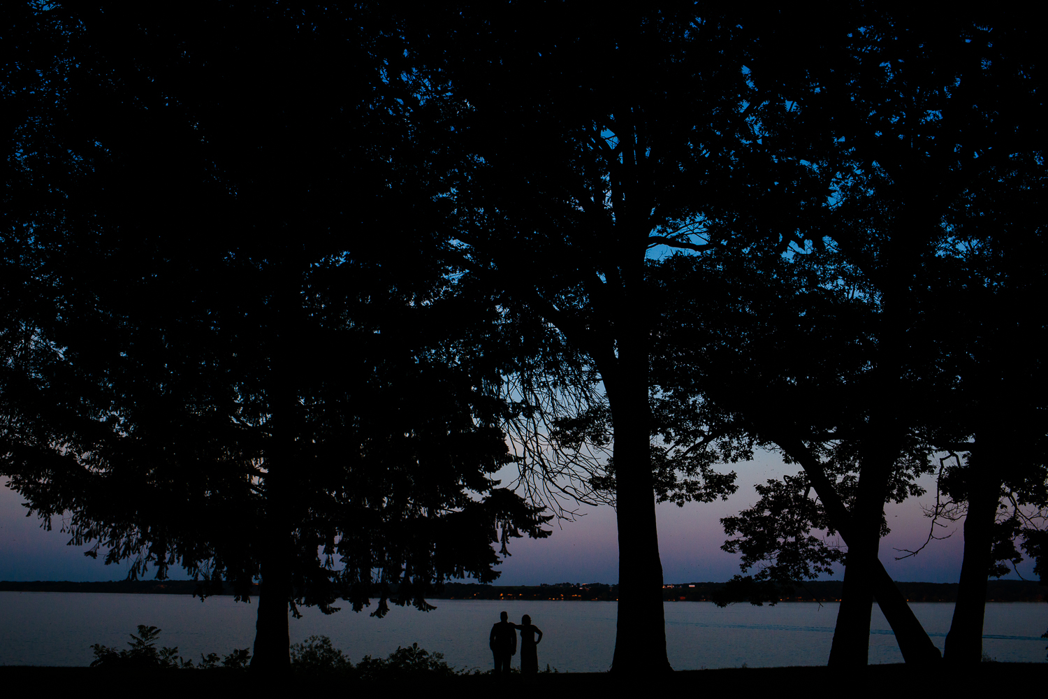 Silhouette of bride and groom agaisnst Geneva Lake.
