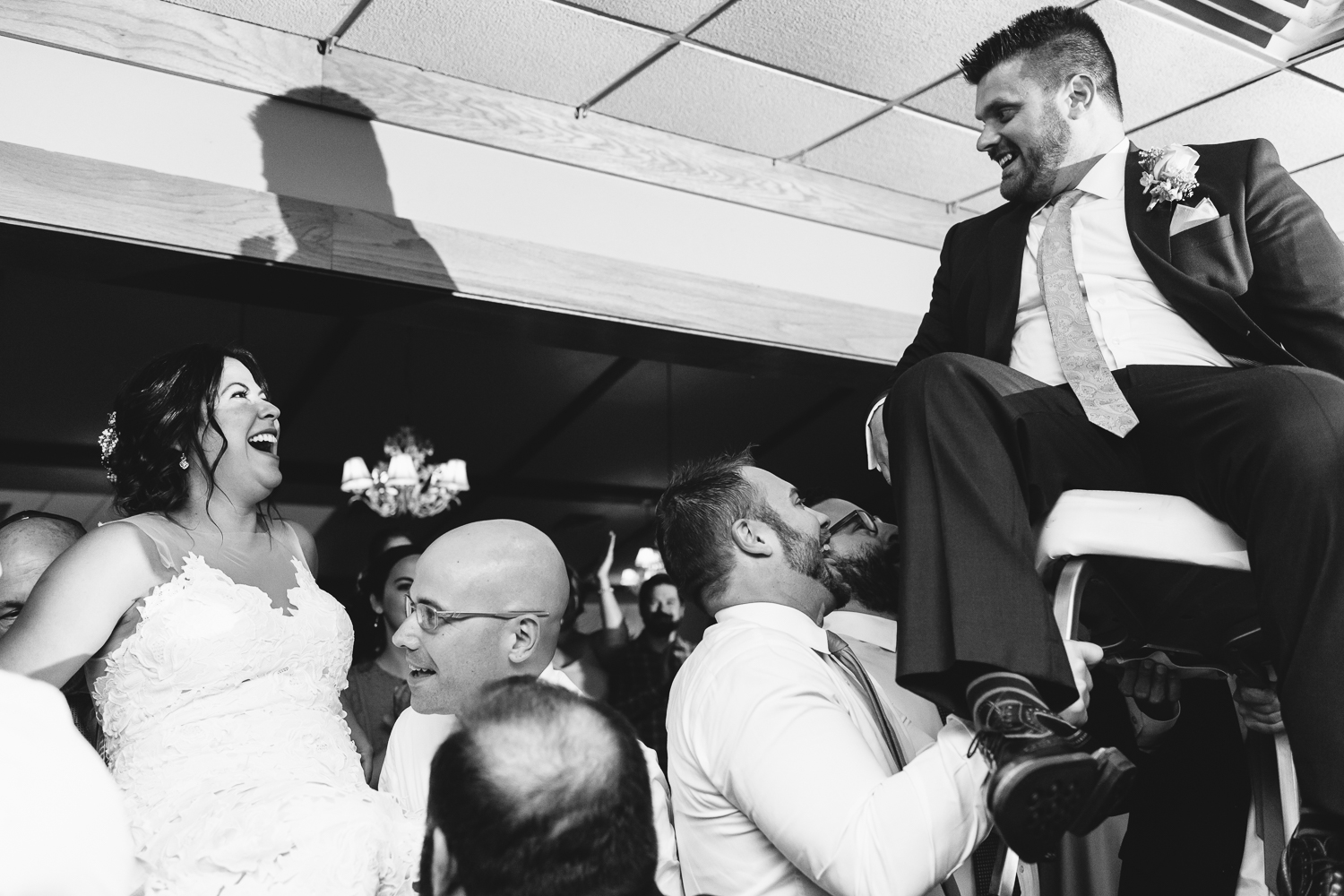 Black and white image of bride and groom getting lifted up on chairs during the Horah.