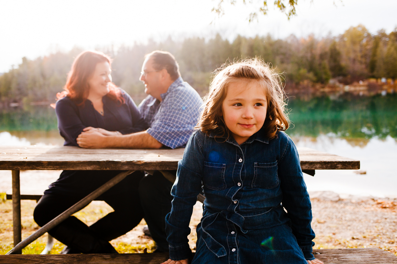 Young girl sits on a picnic table bench while mom and dad sit behind her smiling. They are at Green Lakes State Park.