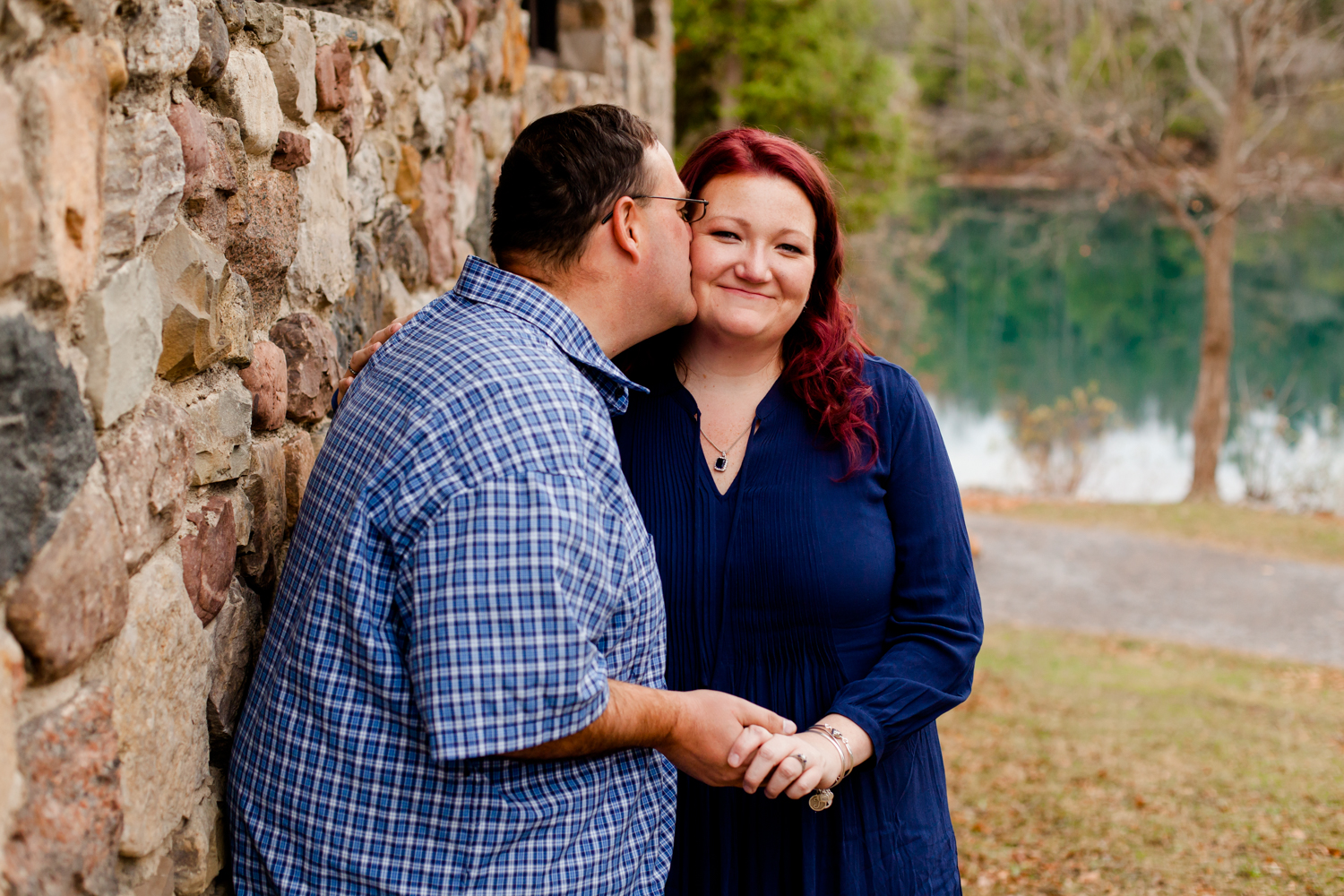 Man kisses his fiance on the cheek during their engagement session. They both are wearing navy blue tops.