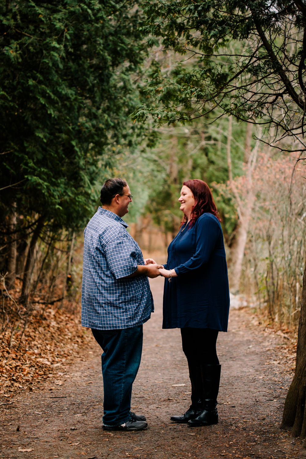 Portrait of a man and woman holding hands surrounded by green trees.