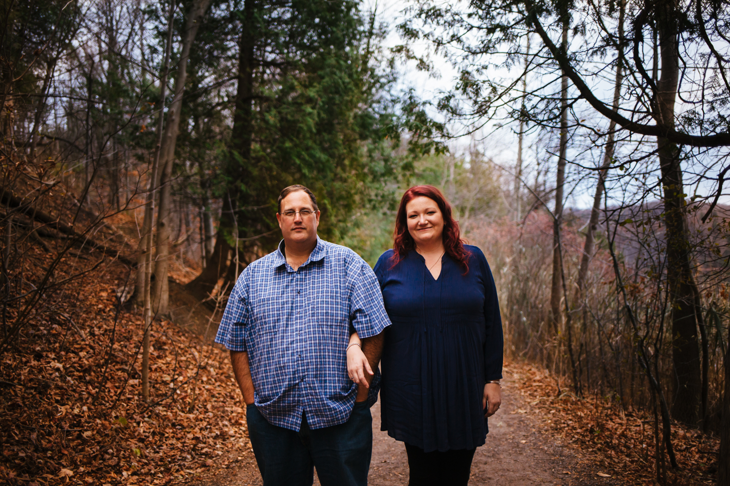 Engagement photograph of man and woman wearing navy blue shirts. They are in the woods surrounded by trees.