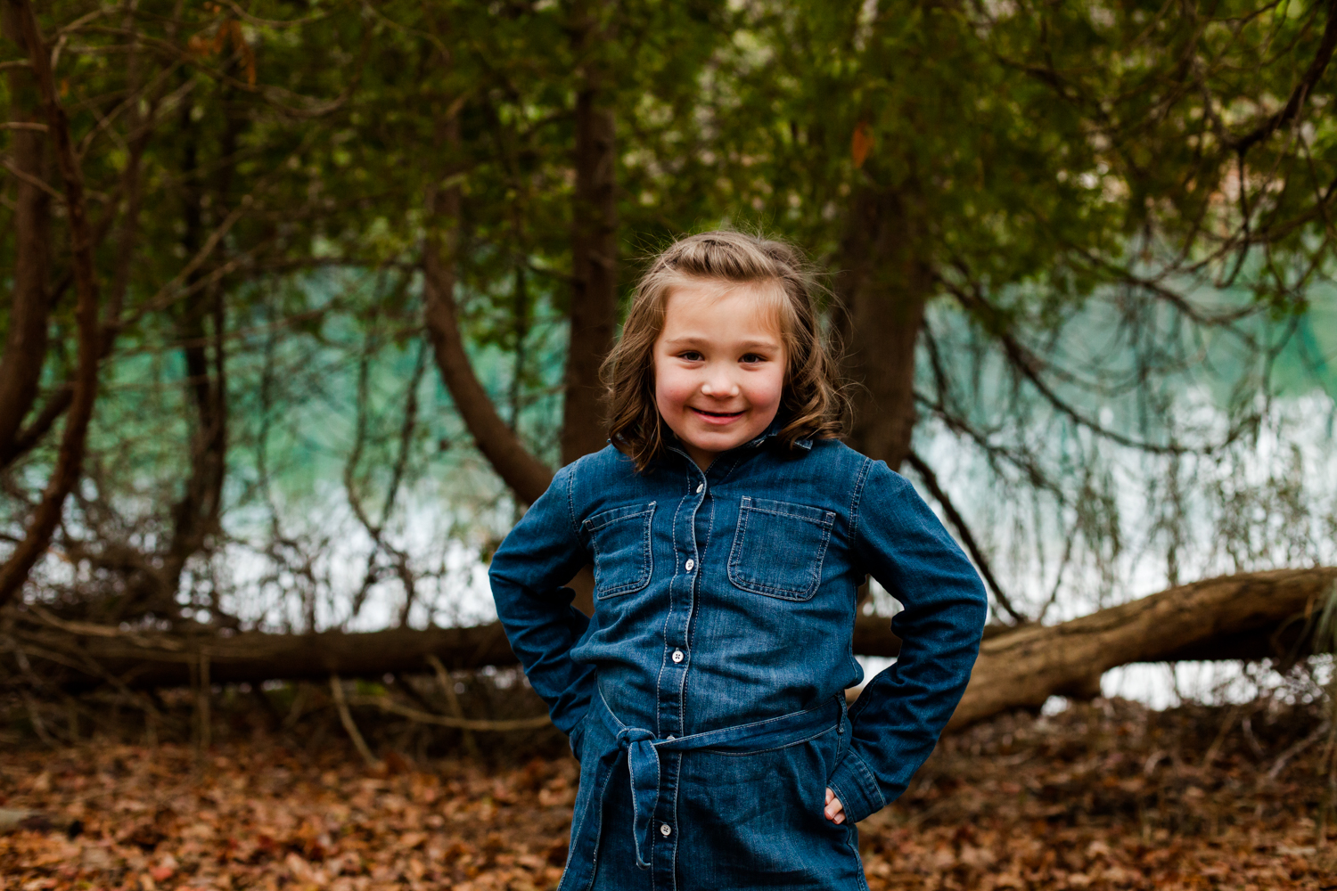 Portrait of a young girl wearing a jean dress. A lake is behind her.