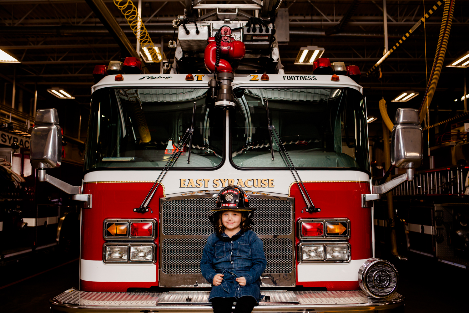 Image of a young girl sitting on a fire truck, she is wearing a fireman helmet.
