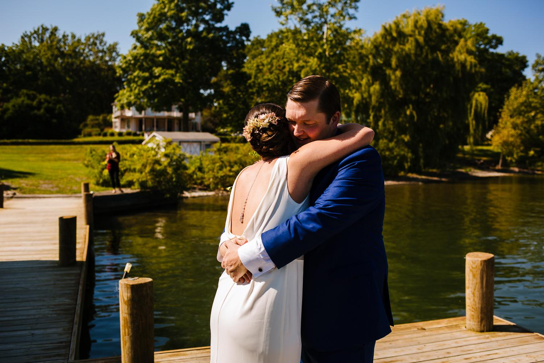 Bride and groom hug on a dock.