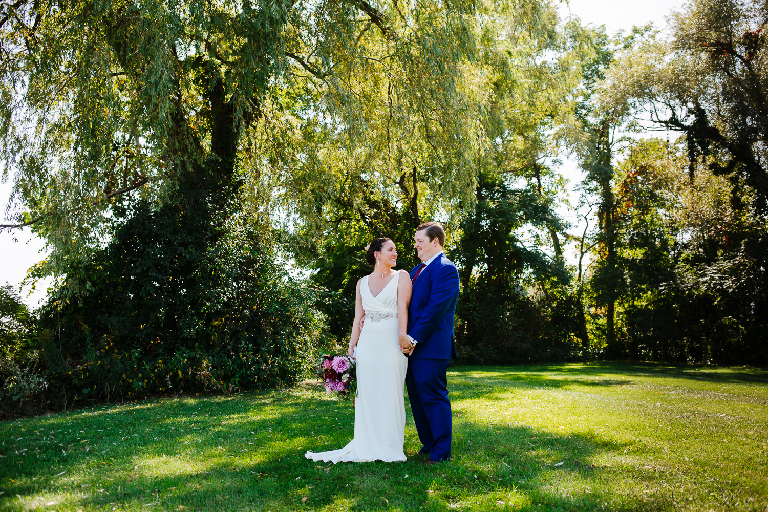 Bride and groom look at each other in front of a willow tree.