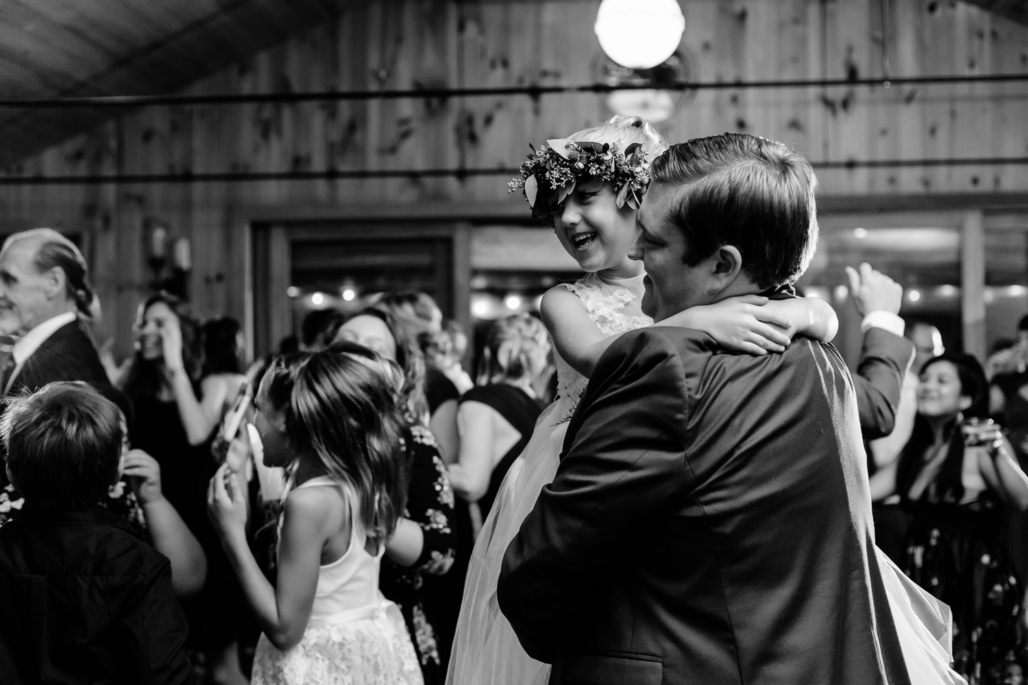 Black and white image of groom dancing with flower girl at a wedding reception.