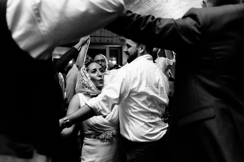 Bride dancing with handkerchief on her head during wedding reception.