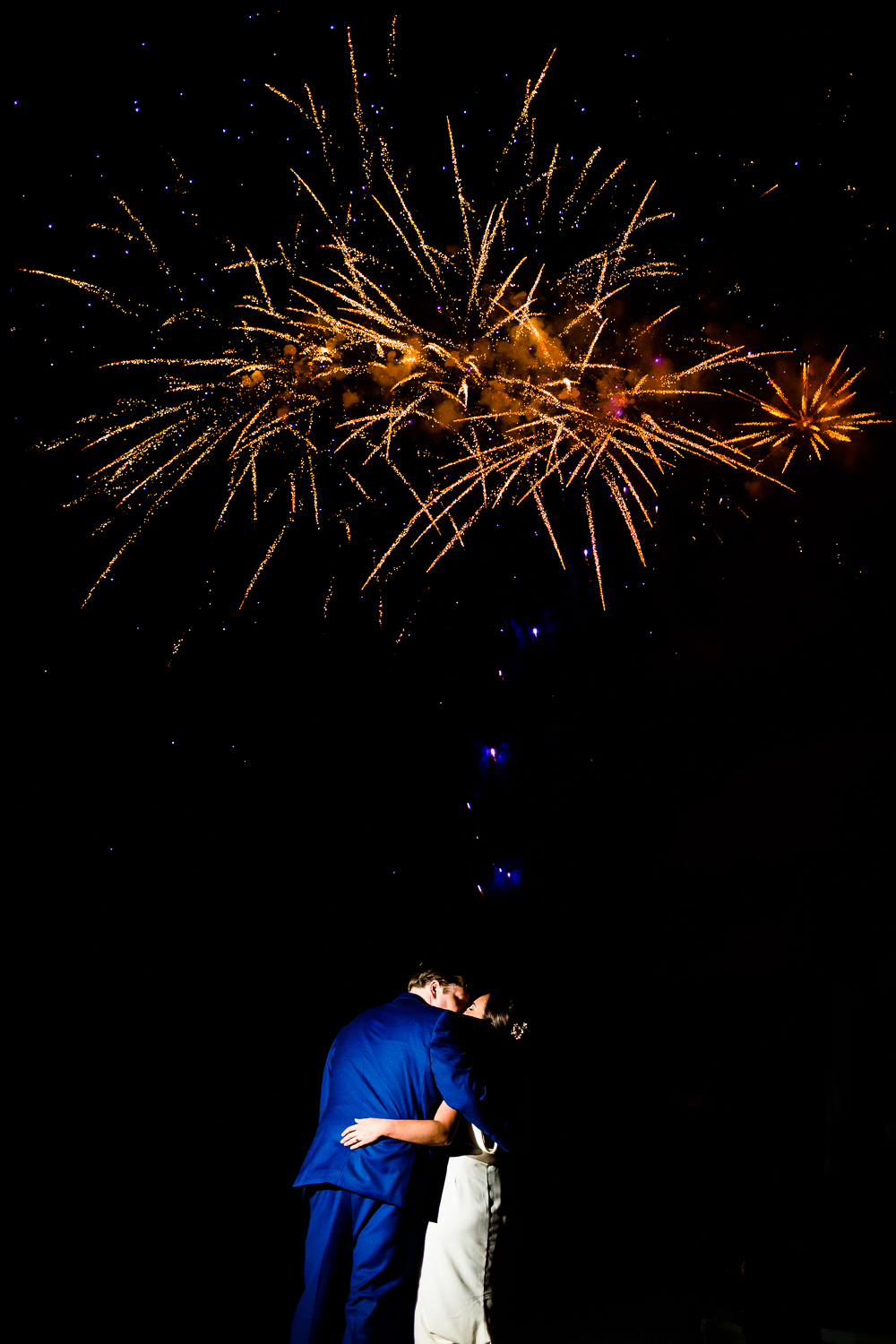 Bride and groom kiss with fireworks above them.