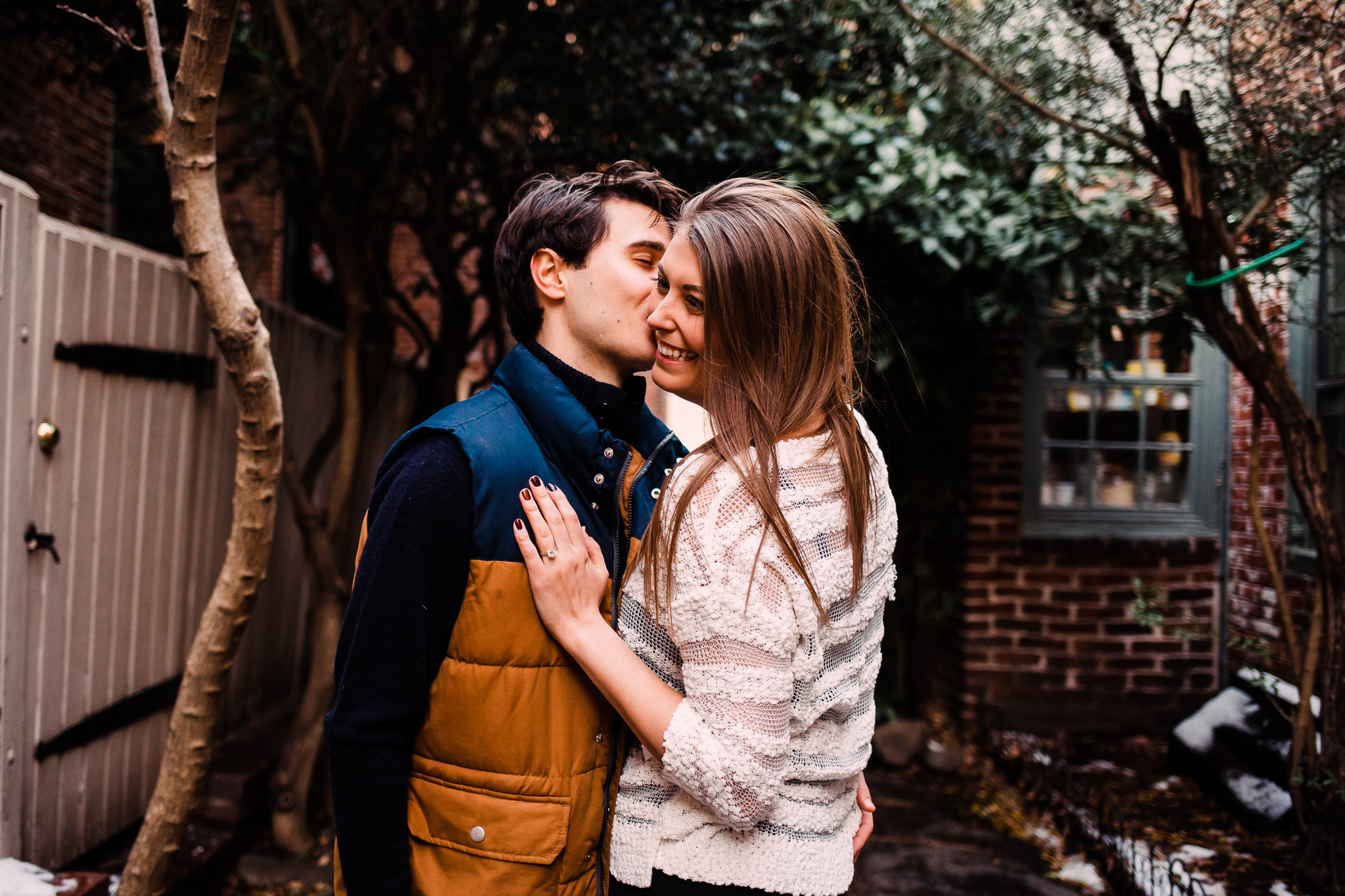 An Engagement photograph in an alleyway. Green leaves are behind the man and woman. The woman has a white sweater on and is smiling. The man has a blue and yellow vest on and is kissing the woman on the cheek. Photo by syracuse wedding photographer calypso rae photography.