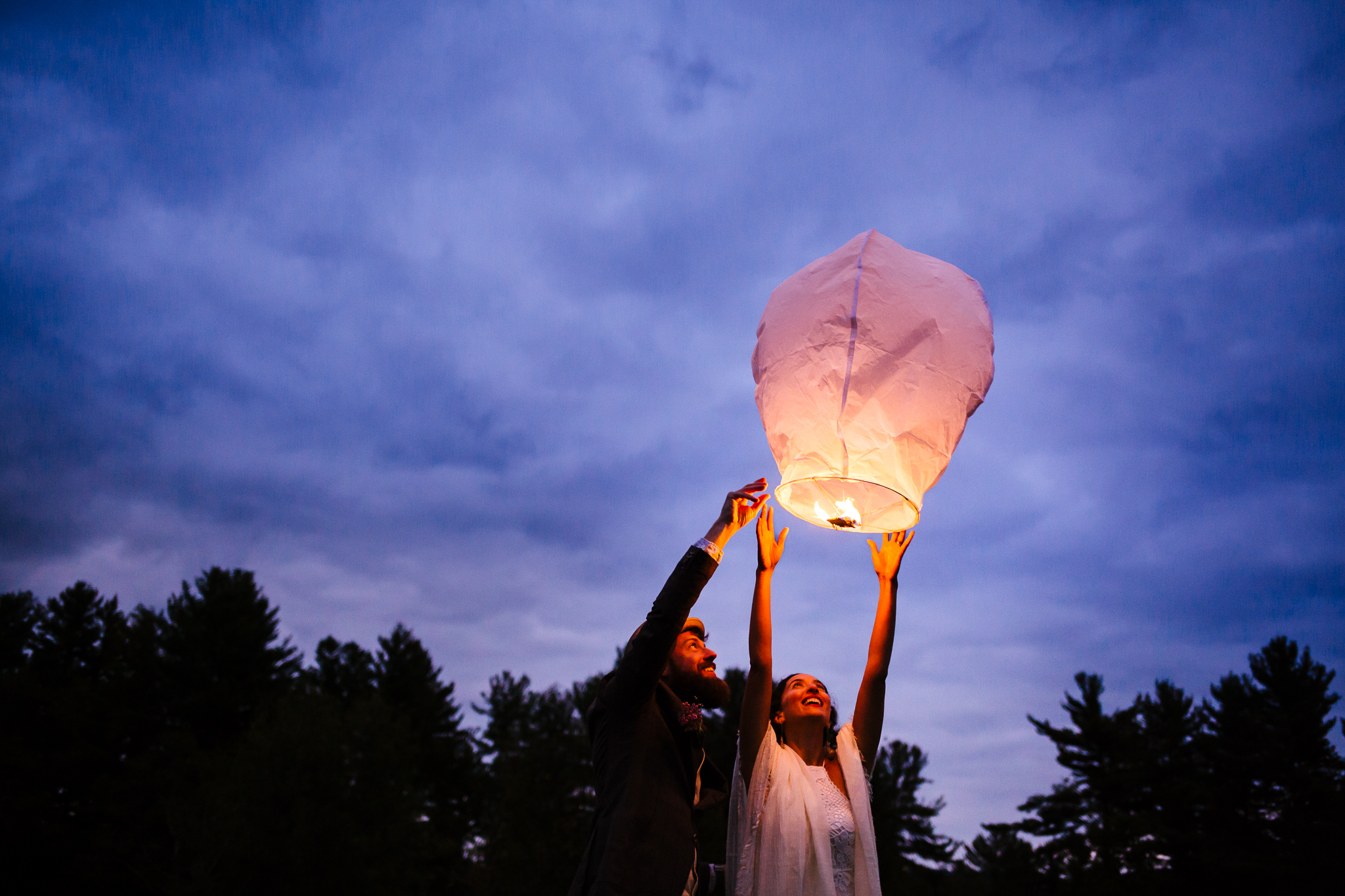 Bride and groom release a chinese lantern into a blue evening sky on their wedding night. The wedding photography is done by a Syracuse wedding photographer.