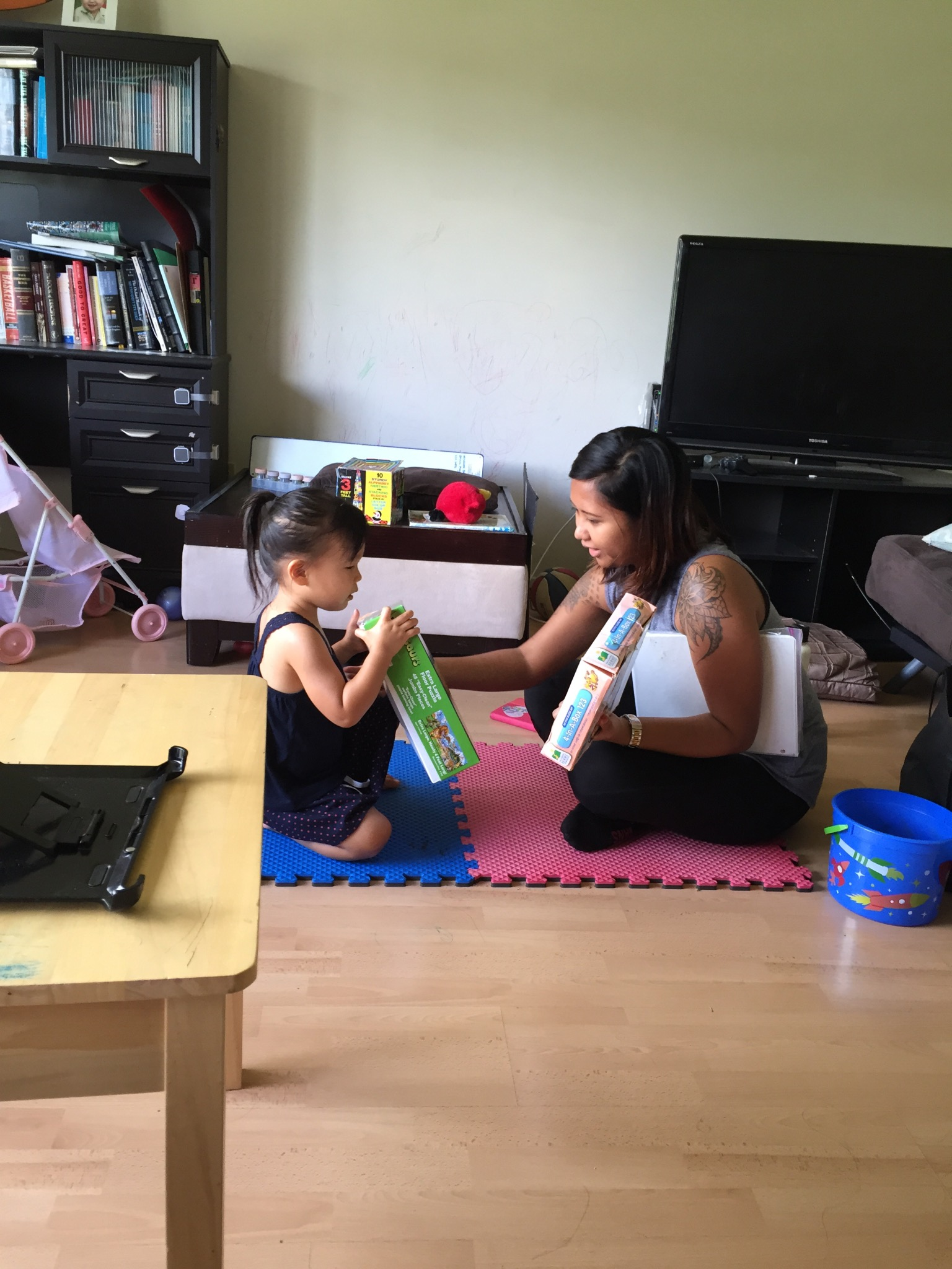 Through Early Intervention she learned to communicate through pictures, sign language, and simple words. Here she is telling the teacher which puzzle she wants to do.