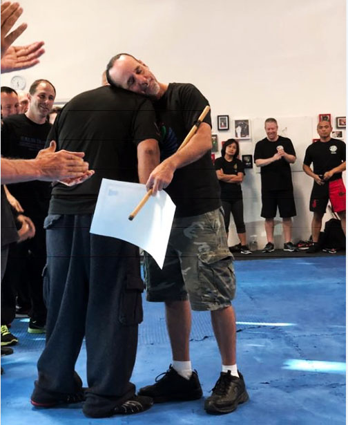 Guro Carlos embracing GM Taboada as he receives his Level 7 certificate at the 2018 World Camp