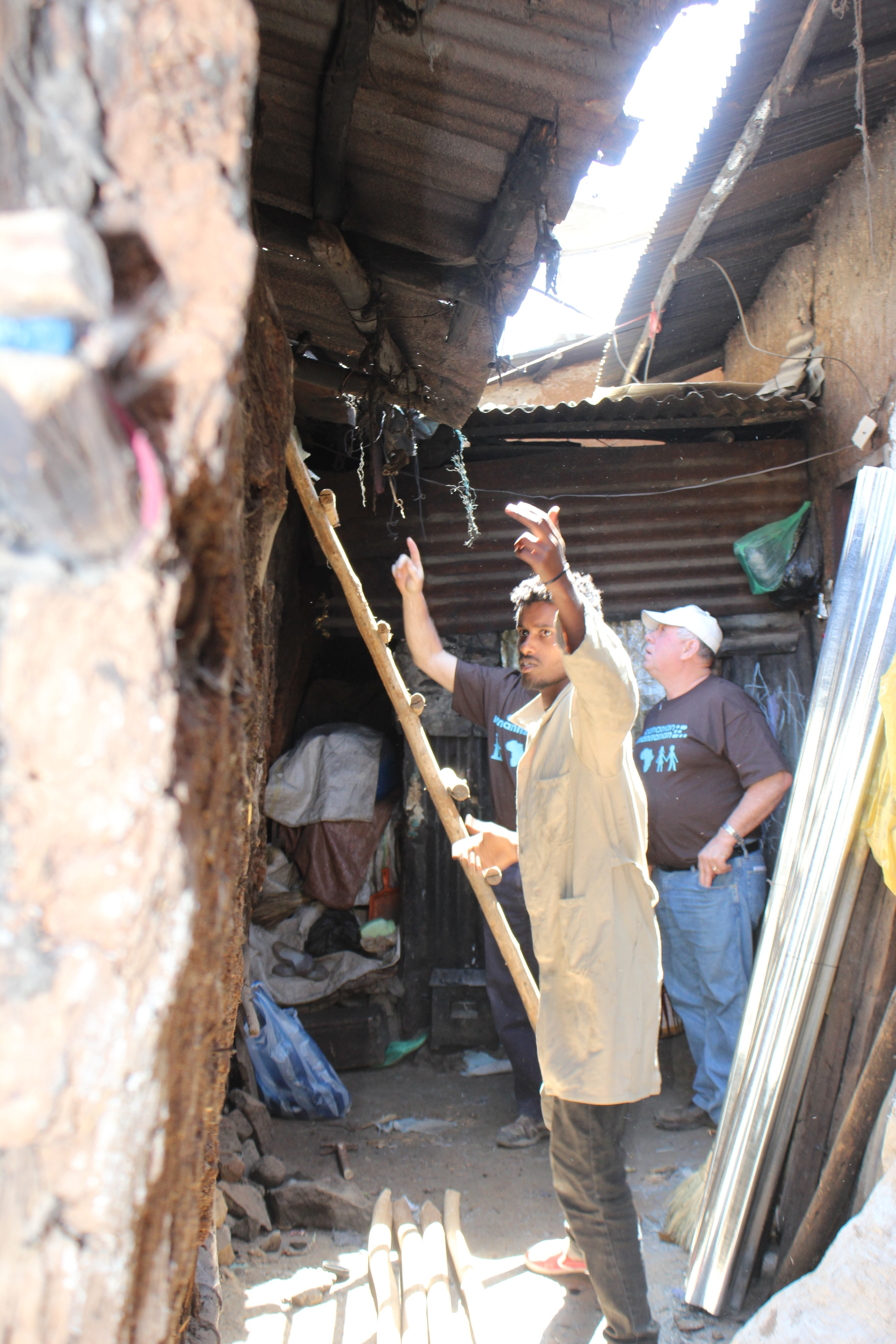 In the confined space, the guys figure out how to dismantle the rusted roof.