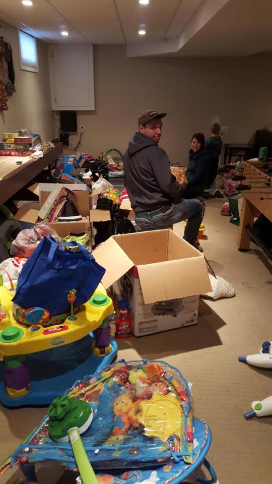 Jeremiah, Dana and son Lars, sort through toy donations in their basement.