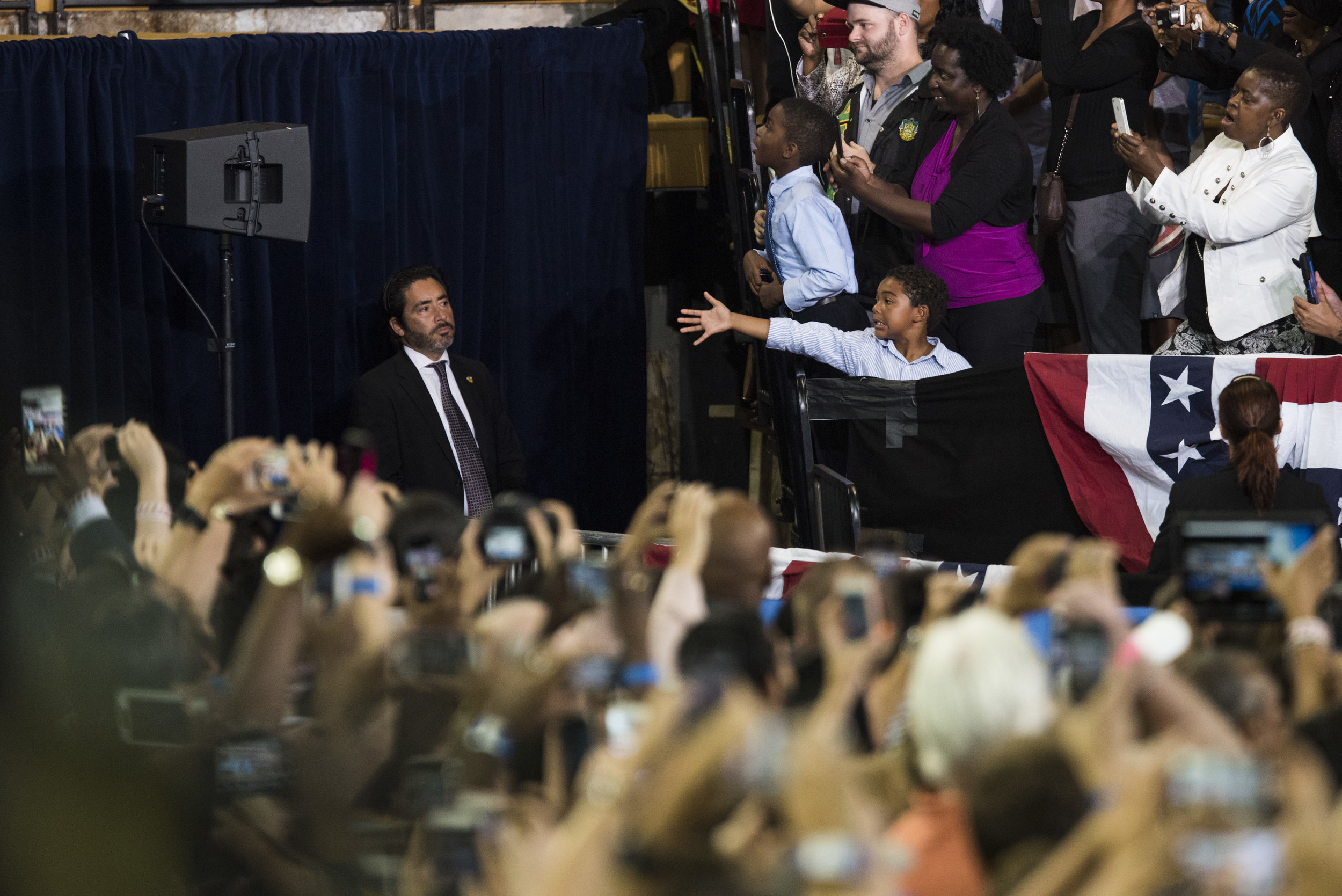 I saw this kid about 2 minutes before President Obama took the stage. I knew he was entering the stage from that side so I was hoping he would get a handshake from the president...