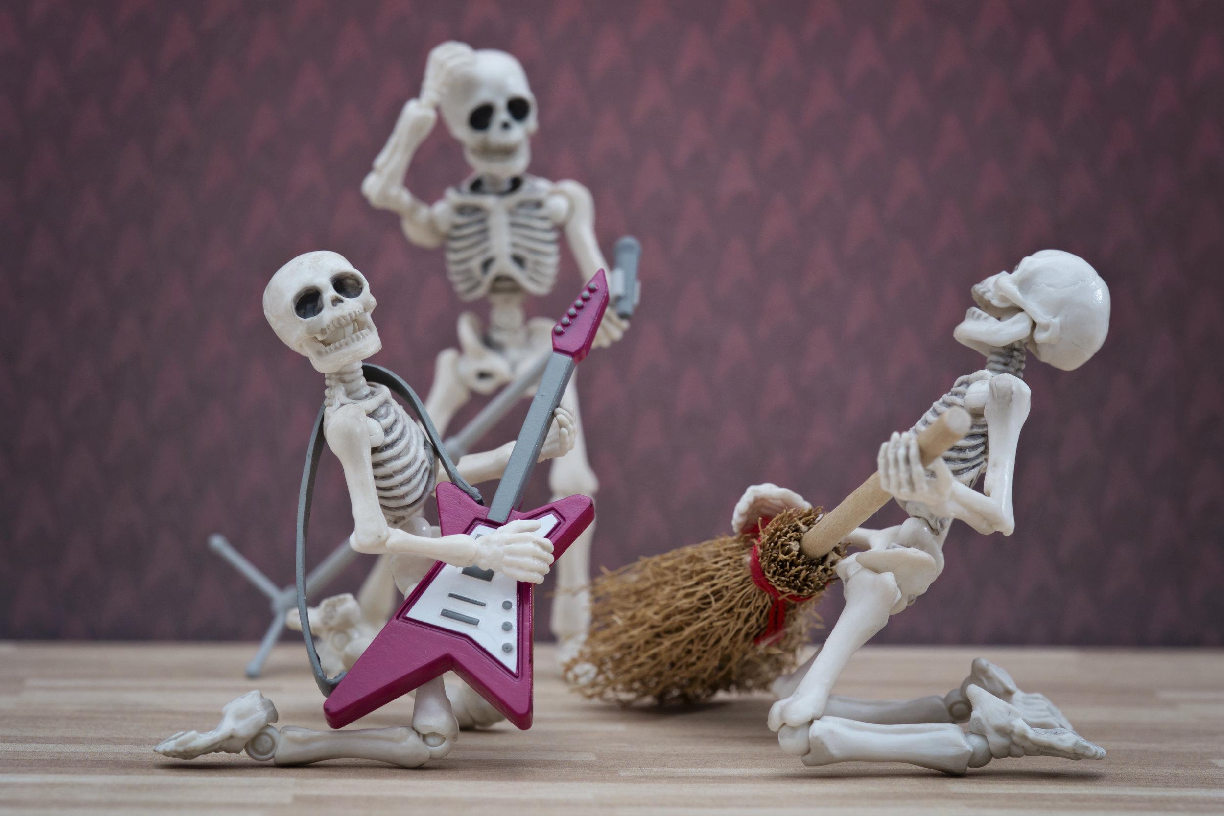 Skeleton playing broom as guitar