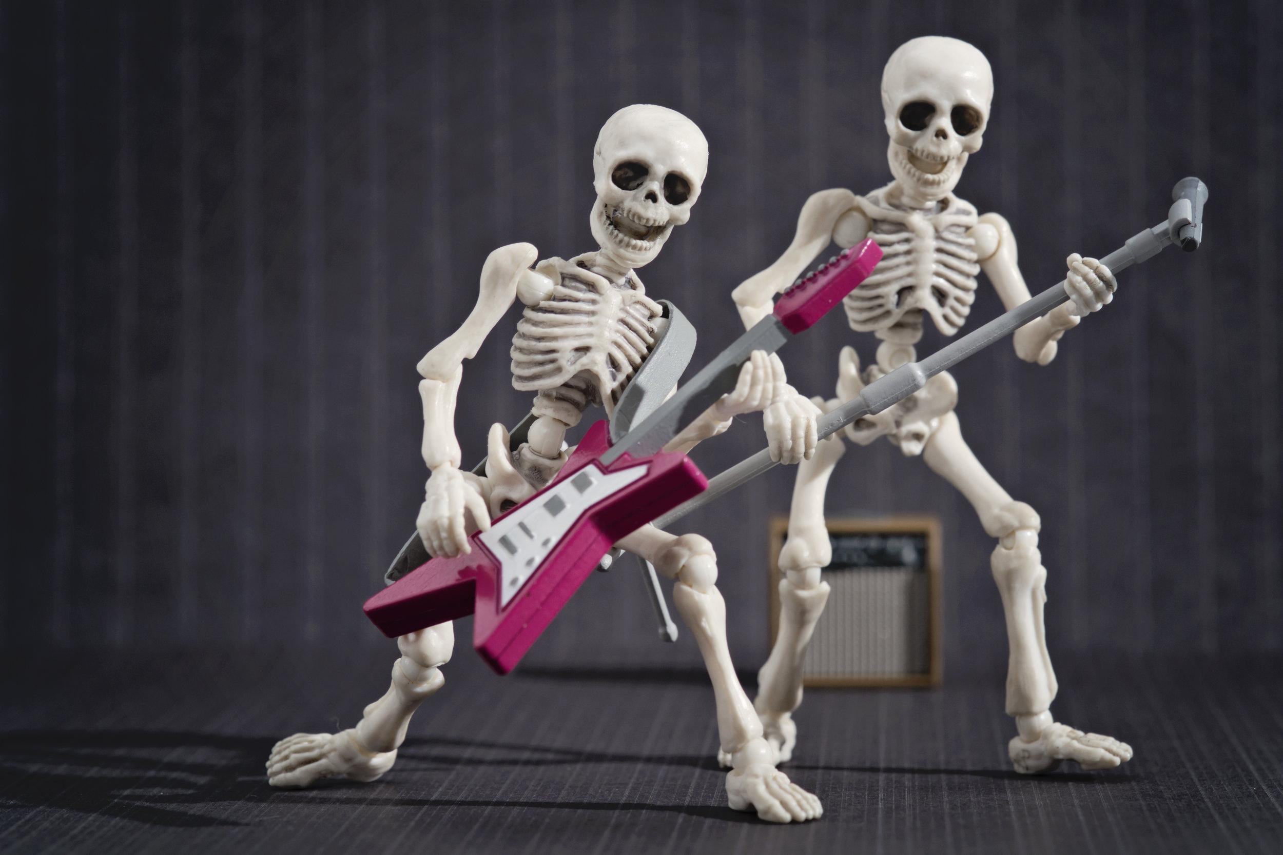 Two skeleton playing rock music