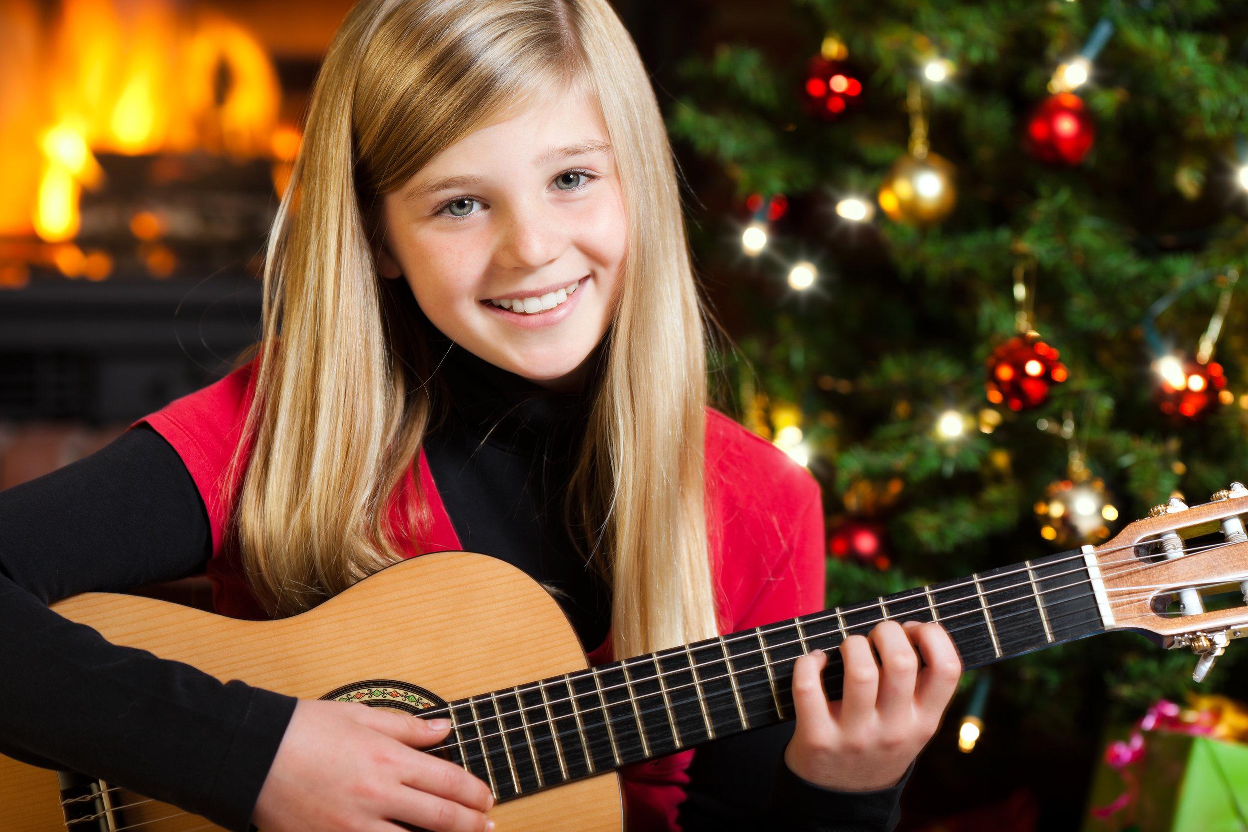 girl playing guitar on christmas eve