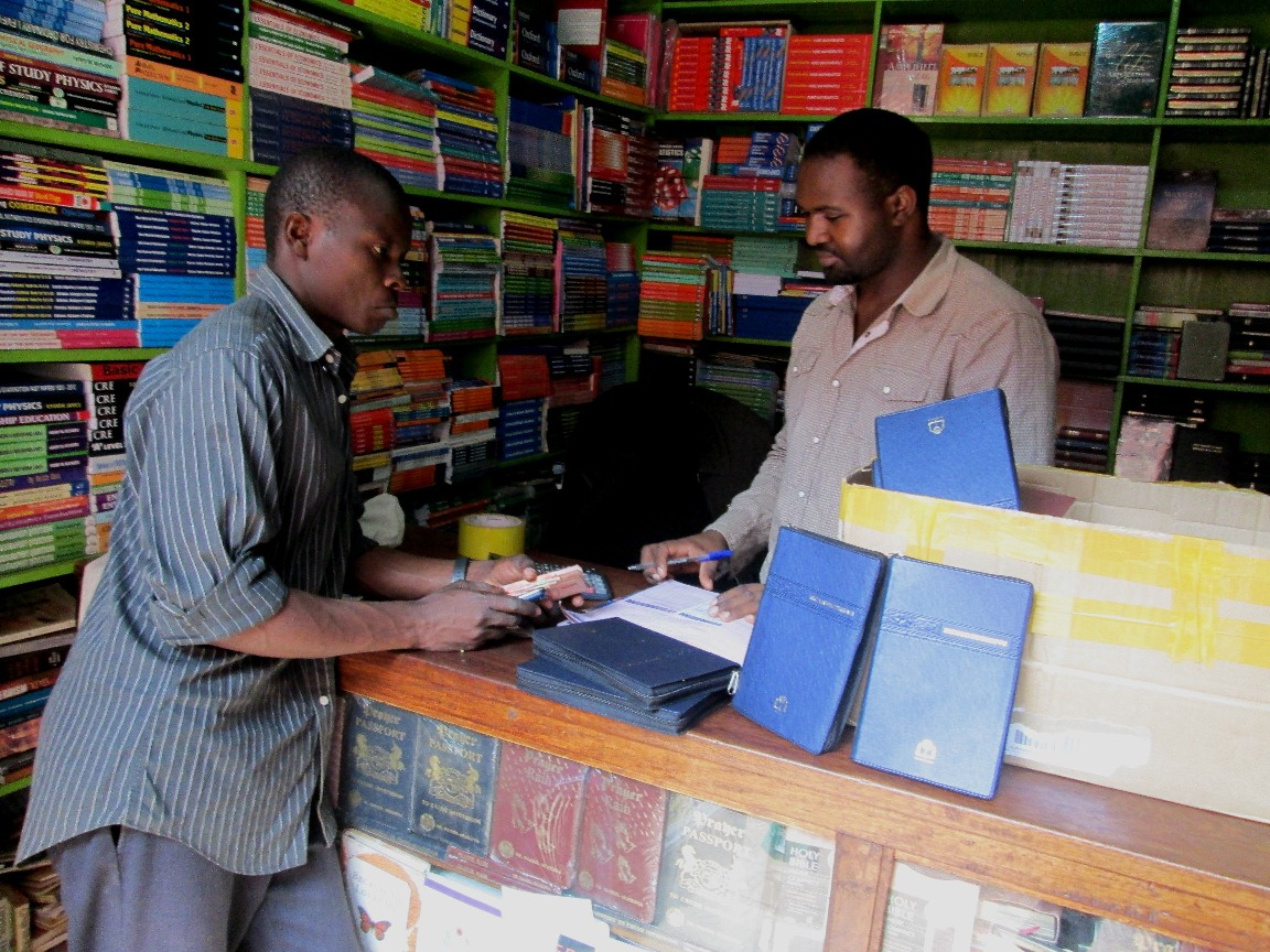Joshua purchasing native language Bibles in Kampala
