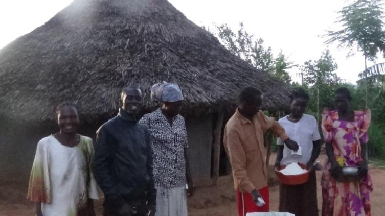Bishop Bita in a group photo as pastor Katandi distributes the posho.12.JPG