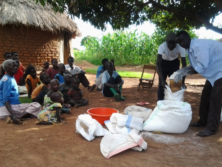 Hungry children and some church members watching Pr. Opure Alex distributing flour.jpg