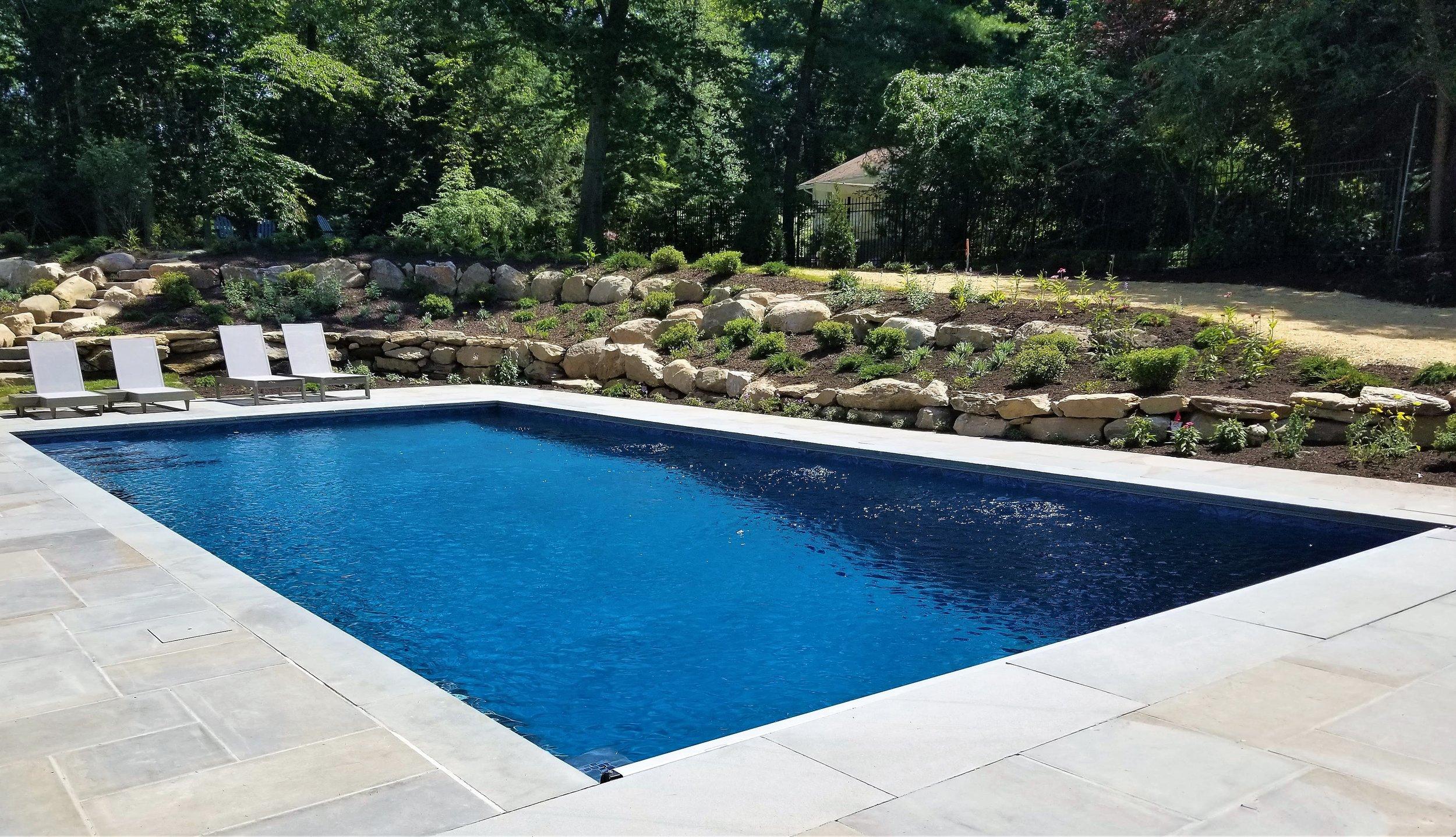 Westport gunite pool with organic boulder wall and plantings.
