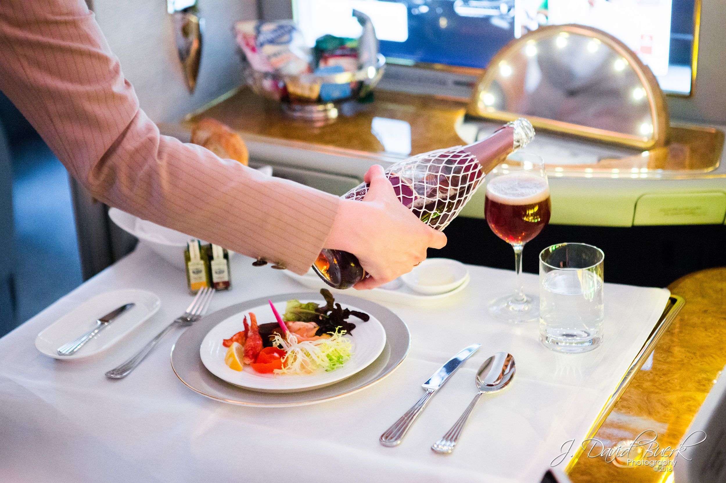 Cabin crew serve champagne in a First Class compartment aboard Emirates' new A380, which began inaugural service between Washington, DC and Dubai on February 23rd, 2016.