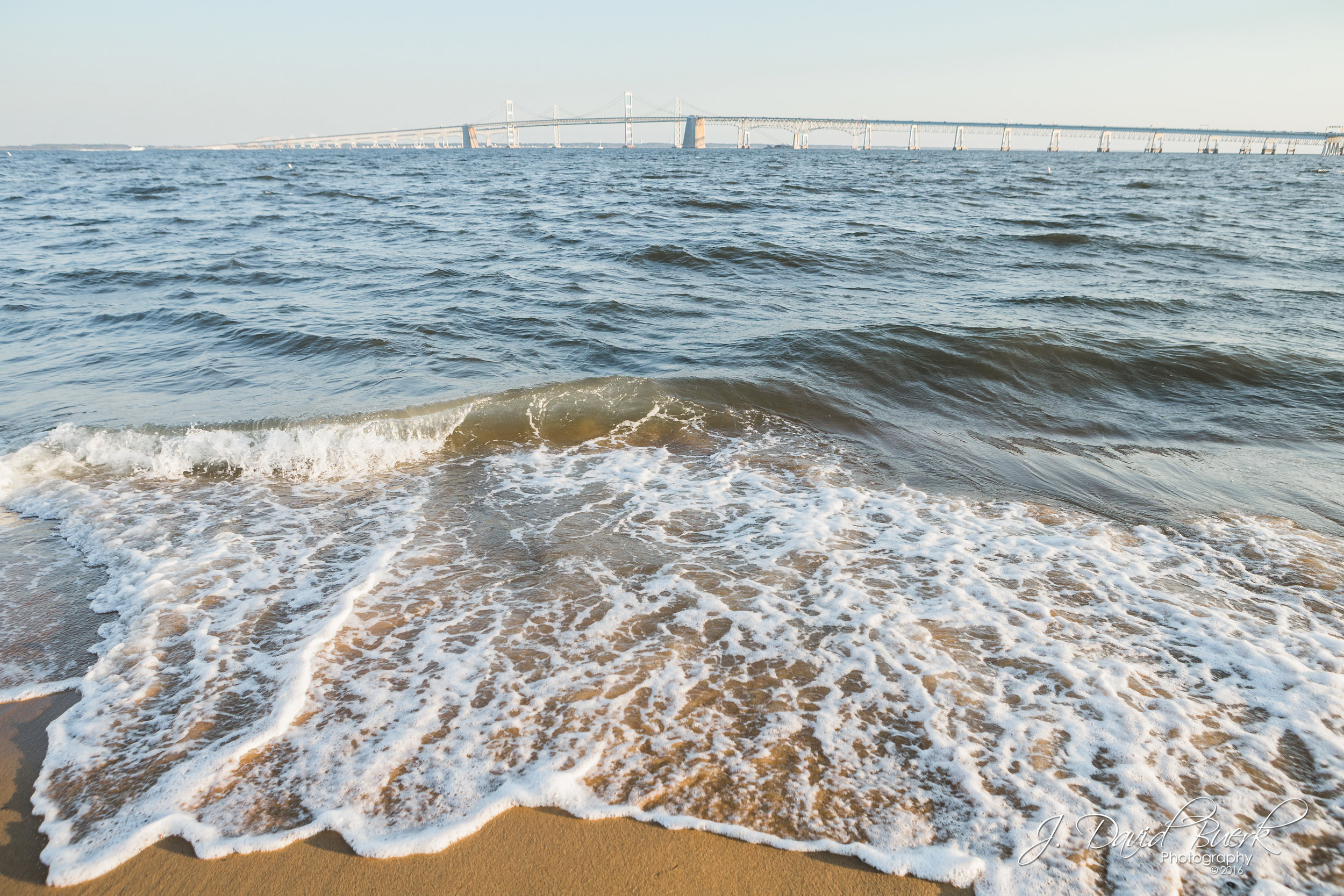 The tide rolls in on the Chesapeake Bay with the Chesapeake Bay Bridge in the distance on a cool Summer day at Sandy Point State Park in Annapolis, Maryland.