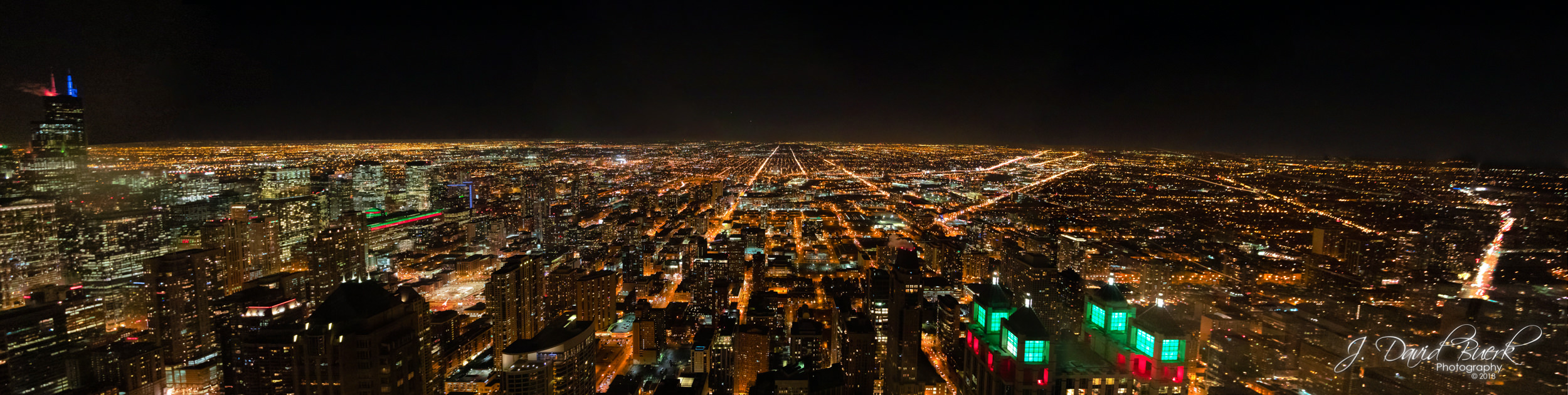 The Chicago, Illinois cityscape skyline at night as seen from atop 875 North Michigan Avenue, colloquially known as the John Hancock Center. Willis Tower (formerly known as Sears Tower) can be seen on the far left lit in red and blue uplighting.