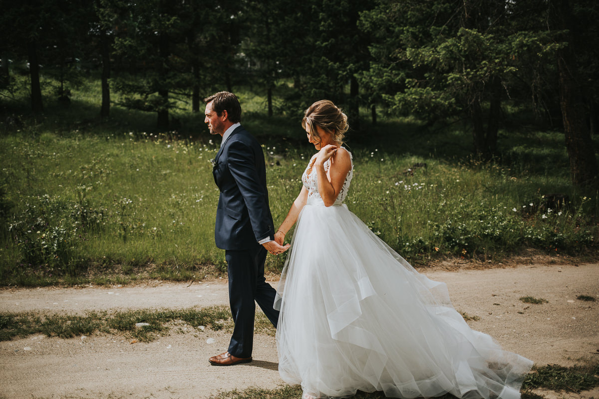 Bride and groom walking sunny Alberta ranch wedding