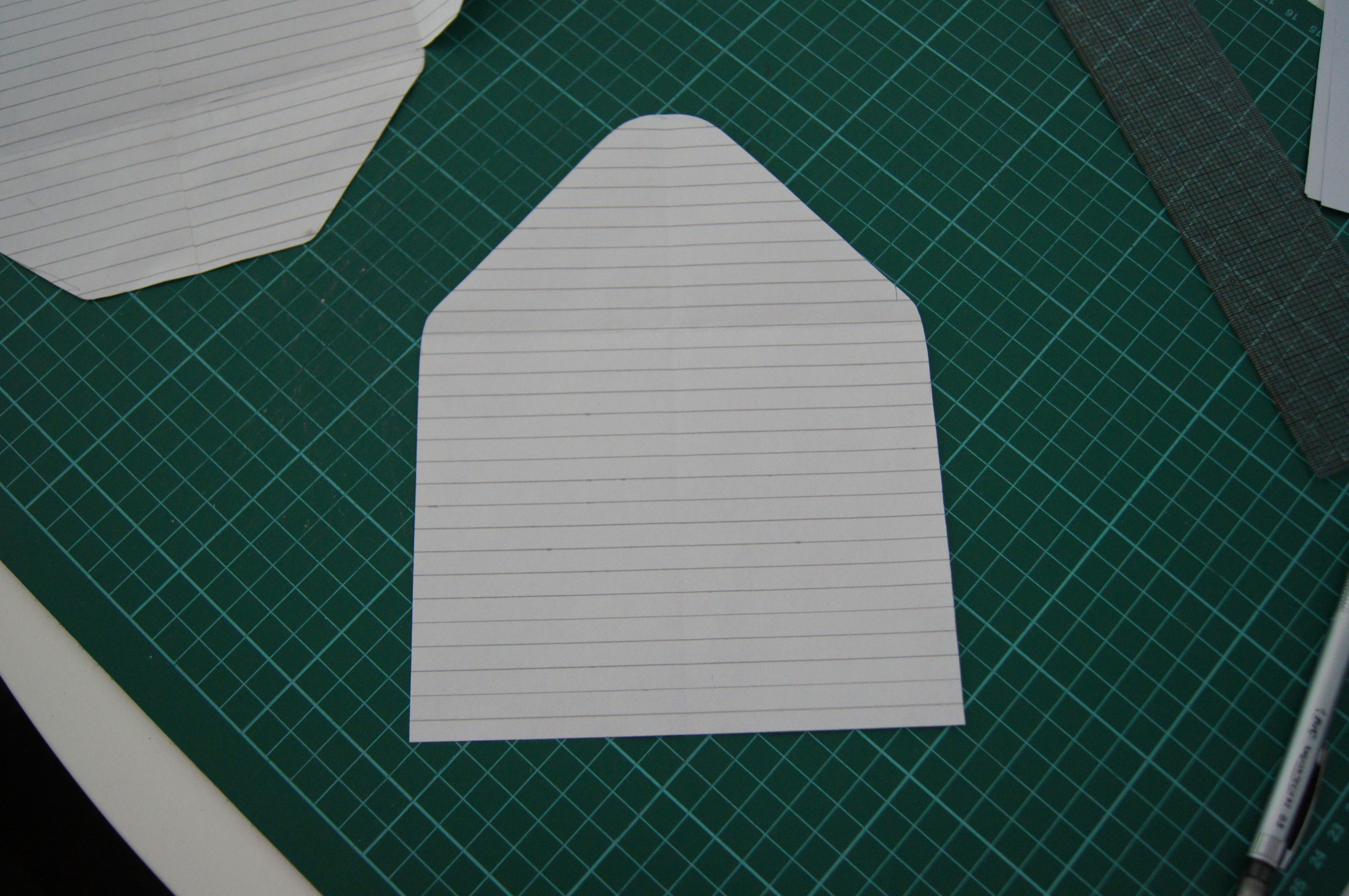 After you have made the template for the shell (navy part), you need to make one for the inside that we shall be using the gold polka dot cardstock for. To do this, I used the above finished template that we are using for the navy shell and traced around just the back section as you can see above on another piece of paper. I then made it a bit smaller so you can see a thin blue strip around the edges. The best way to do this, is to decide how thick you would like the strip and then with a ruler evenly measure around the template, cut along the new line, and then fold the template in half to make sure the sides are perfectly even; and do any trimming if needed.