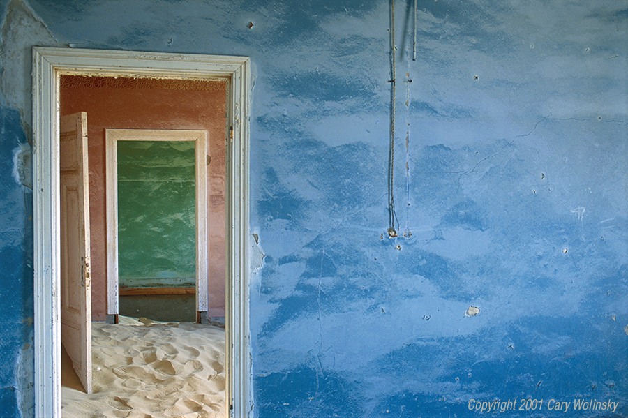 """Sand House Series, Blue, Pink, Green: Kolmanskop, near Luderitz, Namibia, 2001:  I stumbled upon Kolmanskop, an abandoned mining town near Luderitz while working on a story about diamonds for the National Geographic Magazine. In 1908, Namibia was still part of German West Africa. A railroad worker was sweeping sand off a stretch of the rail that hugs the coast and where the Namib Desert meets the sea. He picked up a stone that turned out to be a diamond. This single event transformed a country and triggered a rush of prospectors. Workers literally crawled across the desert, shoulder-to -shoulder harvesting stones in concentrations so rich that, in six years, they found more than 4.6 million carats of diamonds. The German government declared a 290 mille long strip of coastal of land, the """"Sperrgebiet,"""" (the Forbidden Zone) where prospecting was forbidden.  Lively mining towns sprung up overnight, littering the desert with housing, casinos and theaters. By the 1930s, new technology had begun to eliminate jobs: machines were being used to mine coastal sands. Workers returned to Germany and wind-driven sands of the Namib swept into the abandoned towns, filling the tidy workers' rooms, and scouring brightly painted walls into dreamscapes.Photo by Cary Wolinsky"""