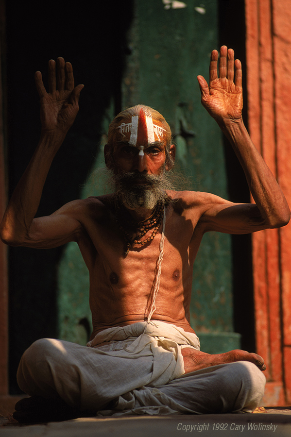 An Indian holy man chants on the steps overlooking the Ganges River. He wears a cotton sutra, or sacred thread symbolizing the circle of life