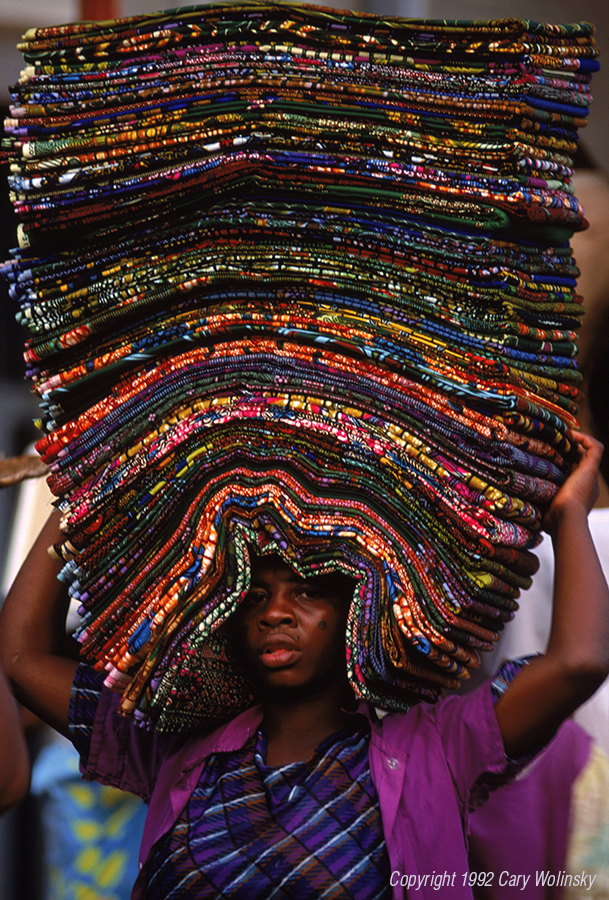 Lomo, Togo, West Africa. A street vendor carrying/balancing wax-printed cotton cloth on her head.