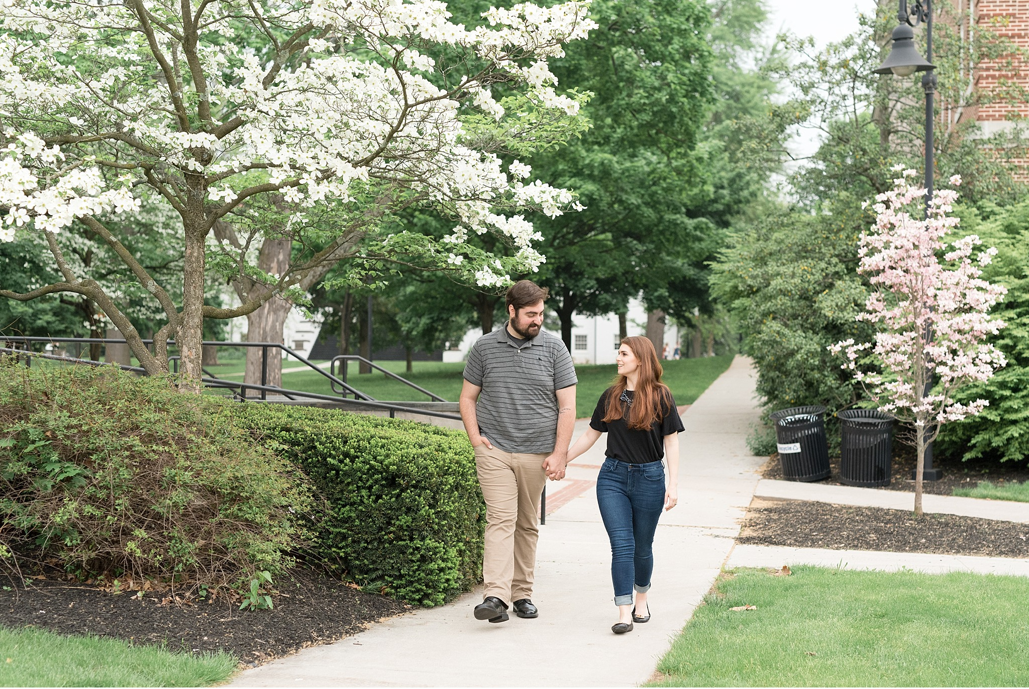 Rainy engagement Gettysburg College Campus bride and groom walking among spring trees photo