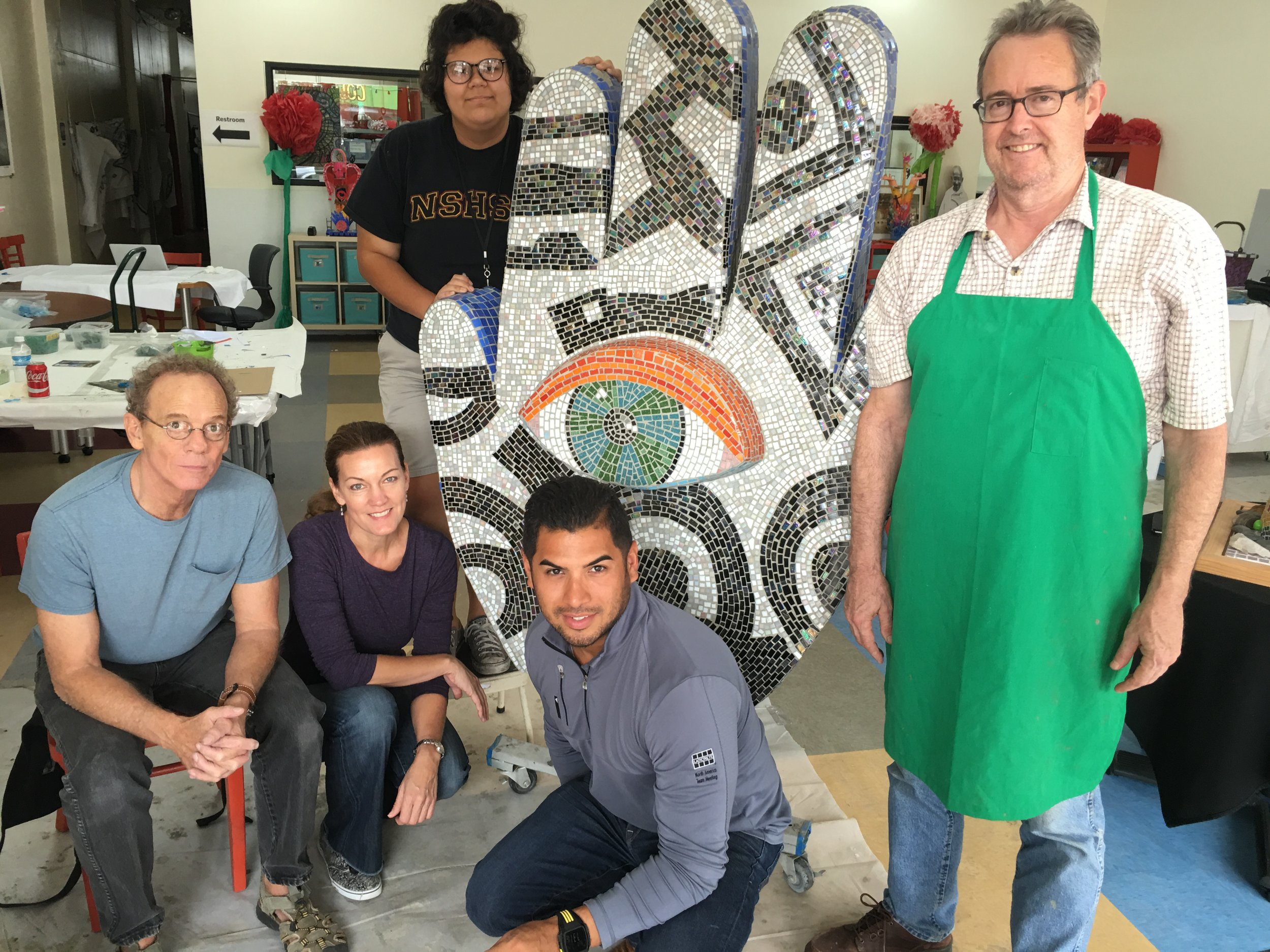 Joe Stokes, lead art instructor, Julie Richey, lead mosaic artist, Maria Patino, student intern, Daniel Diaz, Laticrete rep, and Kelly Nash, 29 Pieces staff artist pose with the completed hand.
