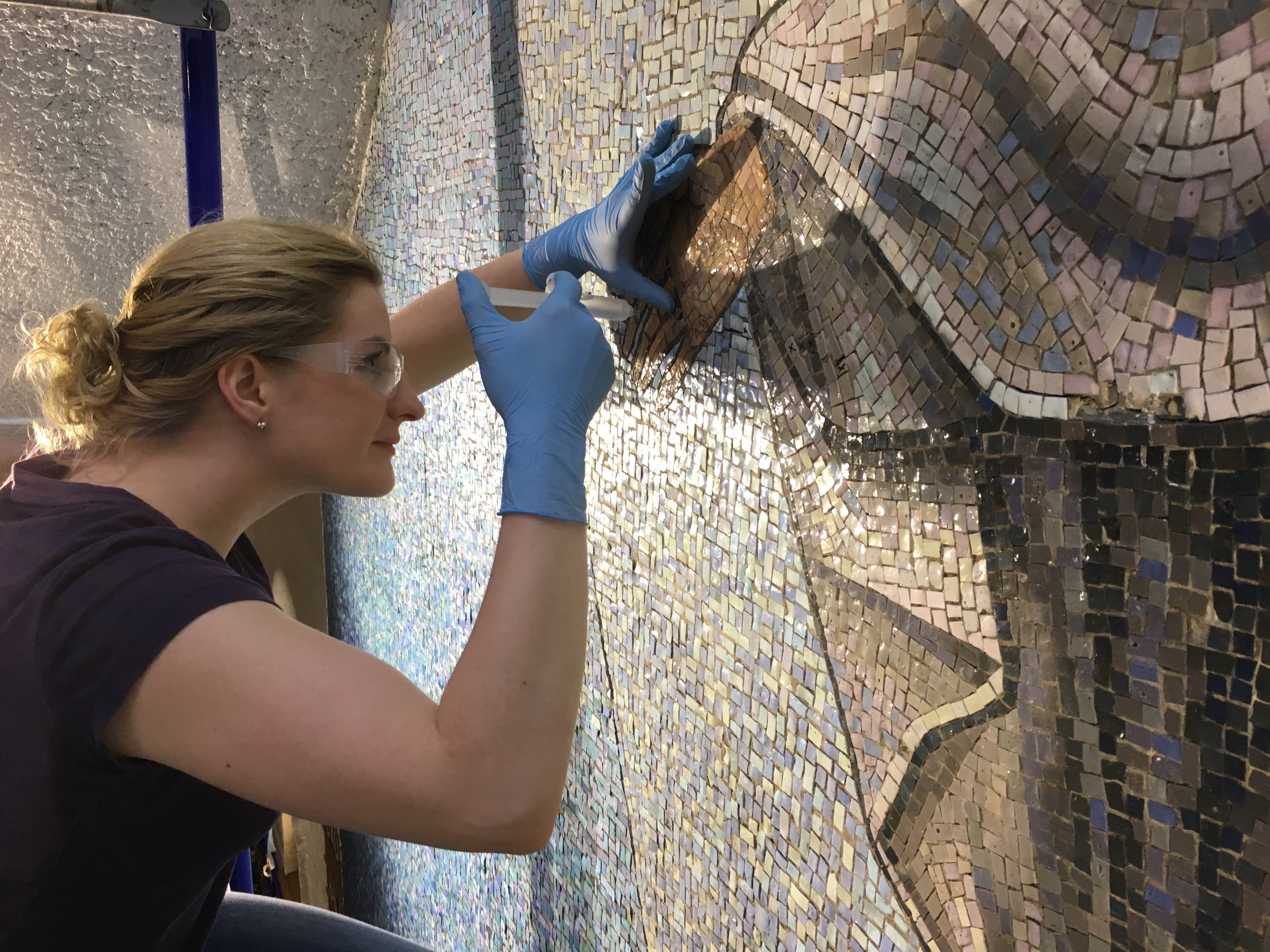 Callie, a conservator with  Art Restorations, Inc.  of Dallas, injects a stabilizer behind the loose tesserae on the Risen Christ mosaic.