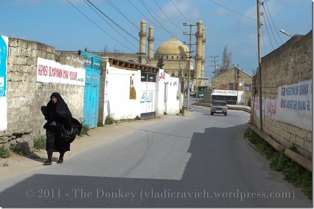 A woman in a chador walks along the streets of Nardaran, with the country's largest pir in the background.