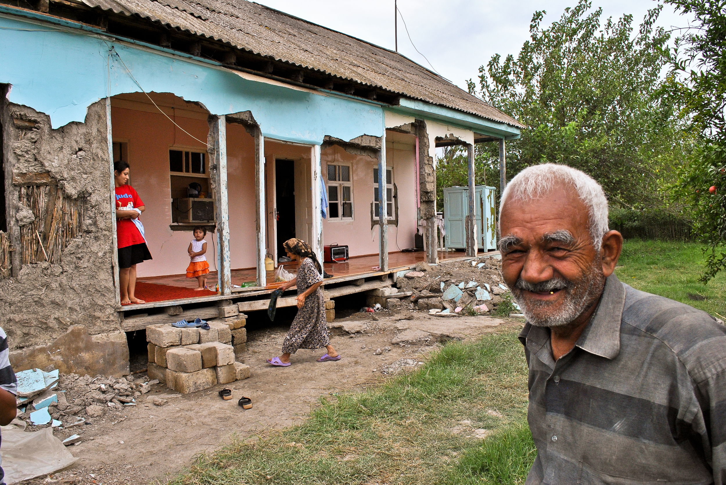A resident of a small village near Sabirabad, with his flood ravaged home behind him.
