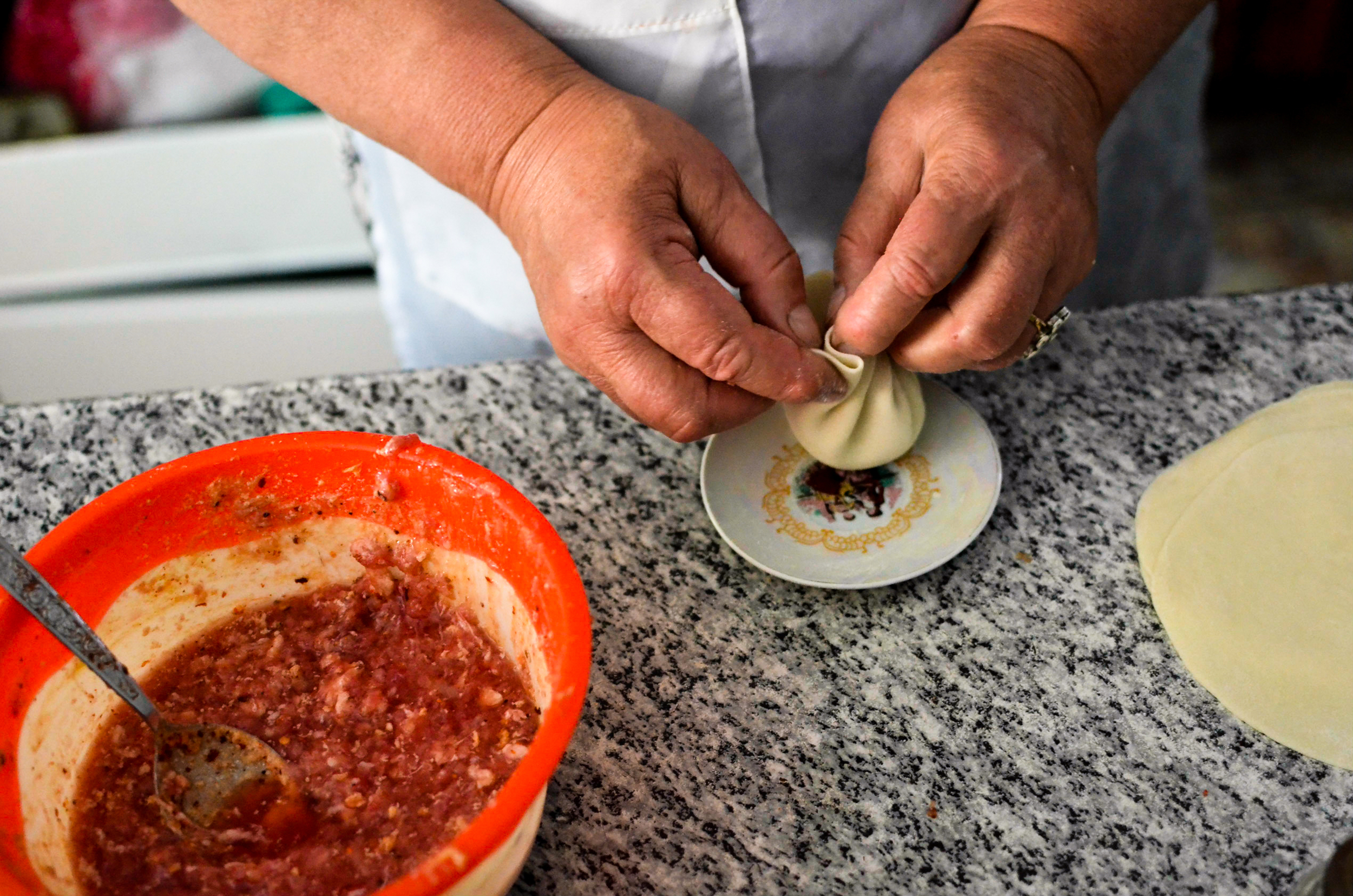 A woman makes khinkali in one of several restuarants converted from garages outside of Tbilisi.