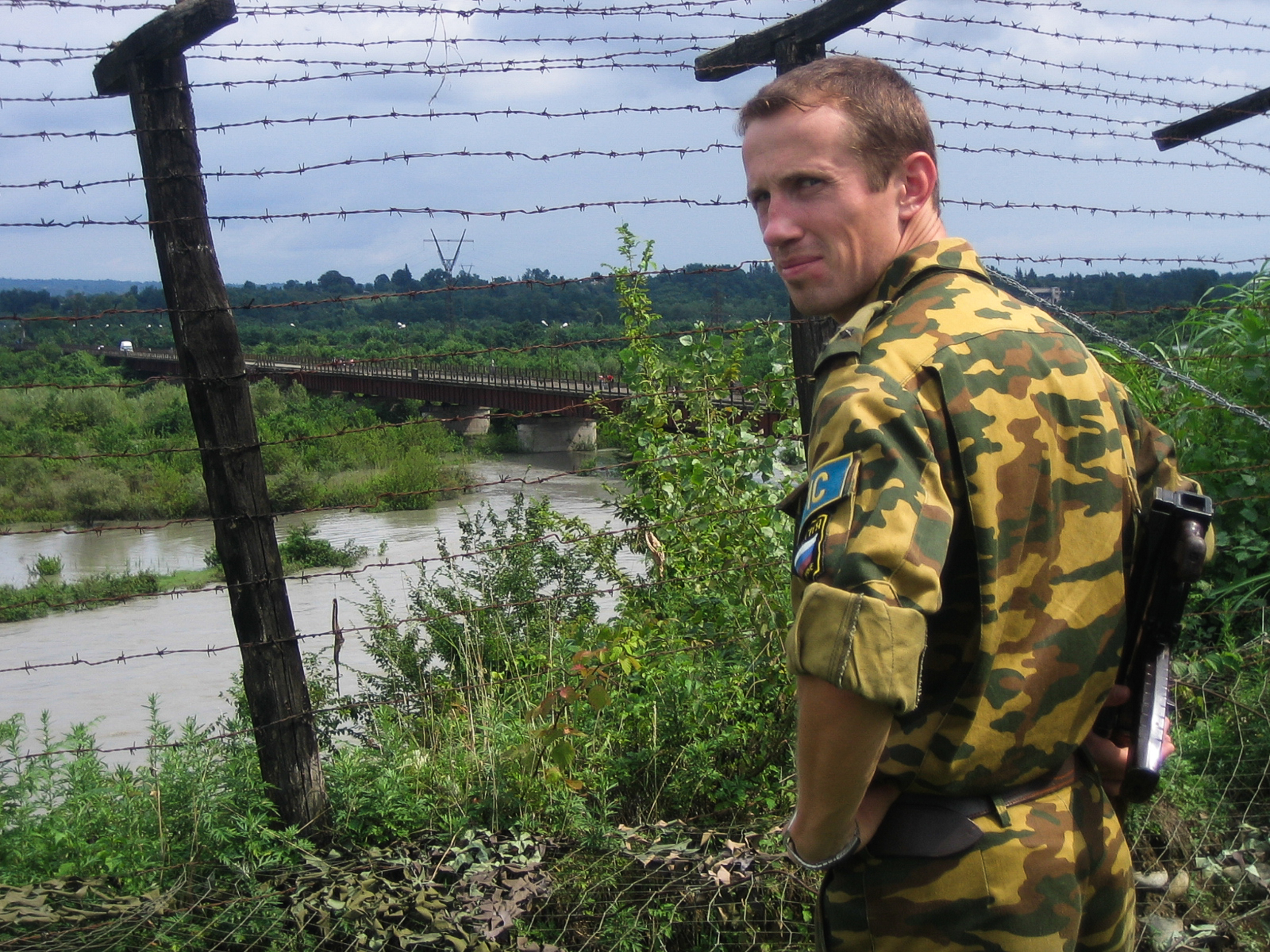A Russian soldier officially serving as a peacekeeper in the heavily militarized border of the seperatist region of Abkhazia, which begins on his side of the Ergneti Bridge. The region is still internationally recognized as part of the Republic of Georgia but has de facto independence, albeit heavily reliant of Russian aid.