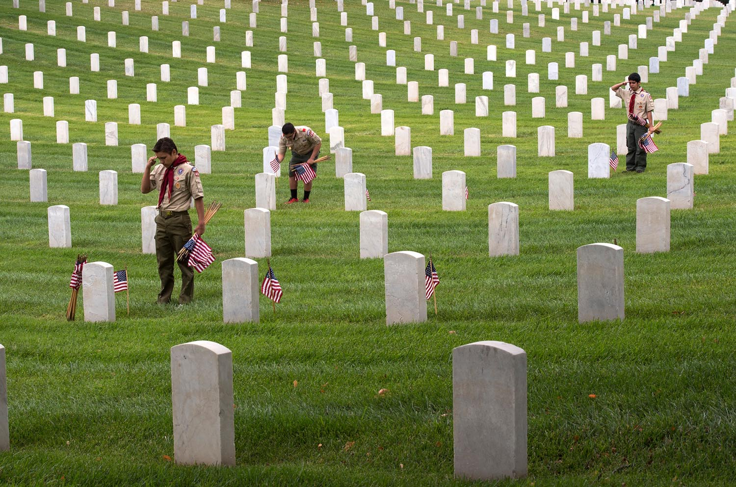 From left, Boy Scouts Troop 400, Dakota Hansen, 14, Christian Pinn, 14, and Kenny Grijalva, 15, place American flags, say the names and render salutes at the Los Angeles National Cemetery on Saturday. Hundreds of L.A. area Boy Scouts, Girls Scouts, Sea Cadets and others place American flags on each grave of over 88,000 war veterans.